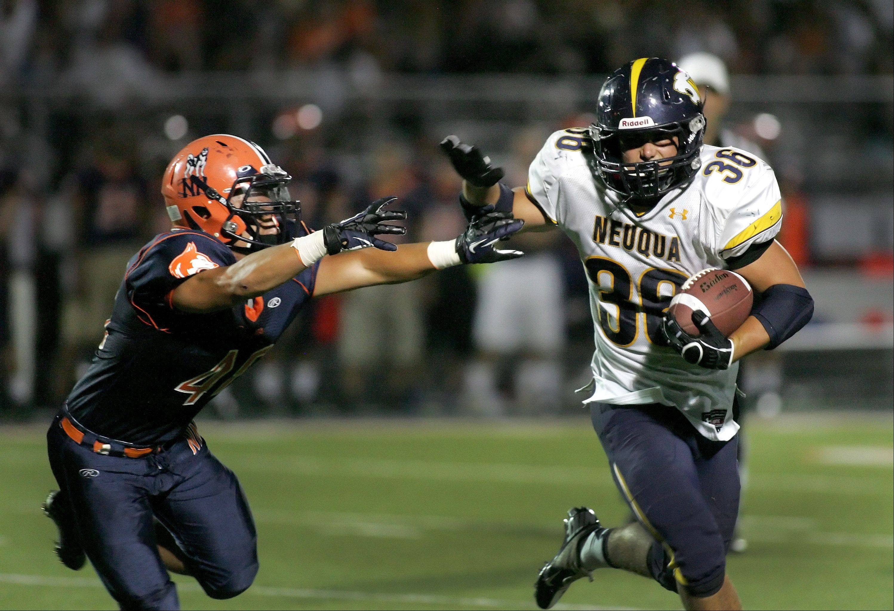Joey Rhattigan of Neuqua Valley, right, holds off Eric Montgomery, left, of Naperville North in football action Friday in Naperville.