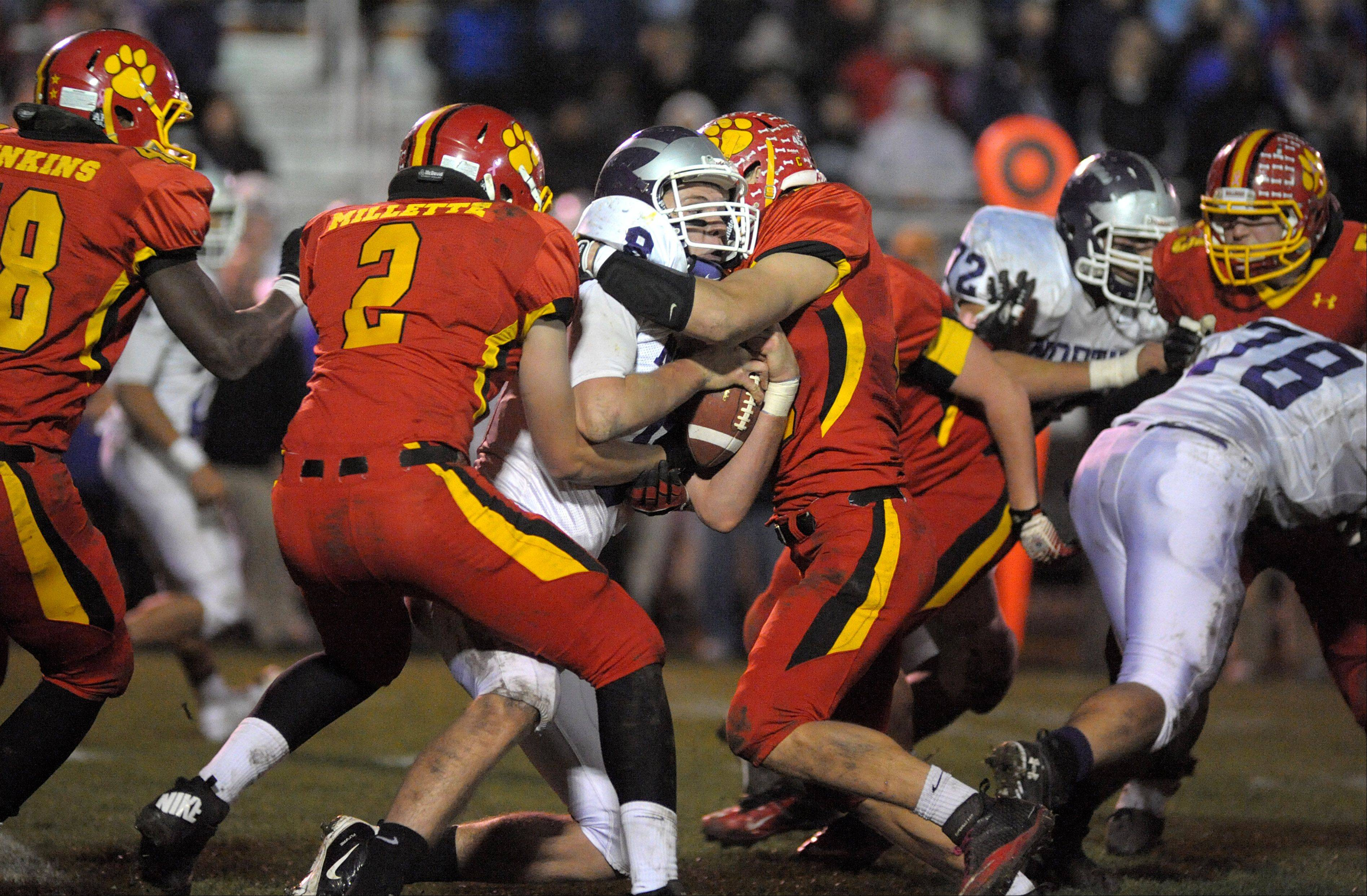 Downers Grove North quarterback David Edwards is sacked by Batavia's James Millette and Cullin Rokos in the fourth quarter of playoff game on Friday, October 26.