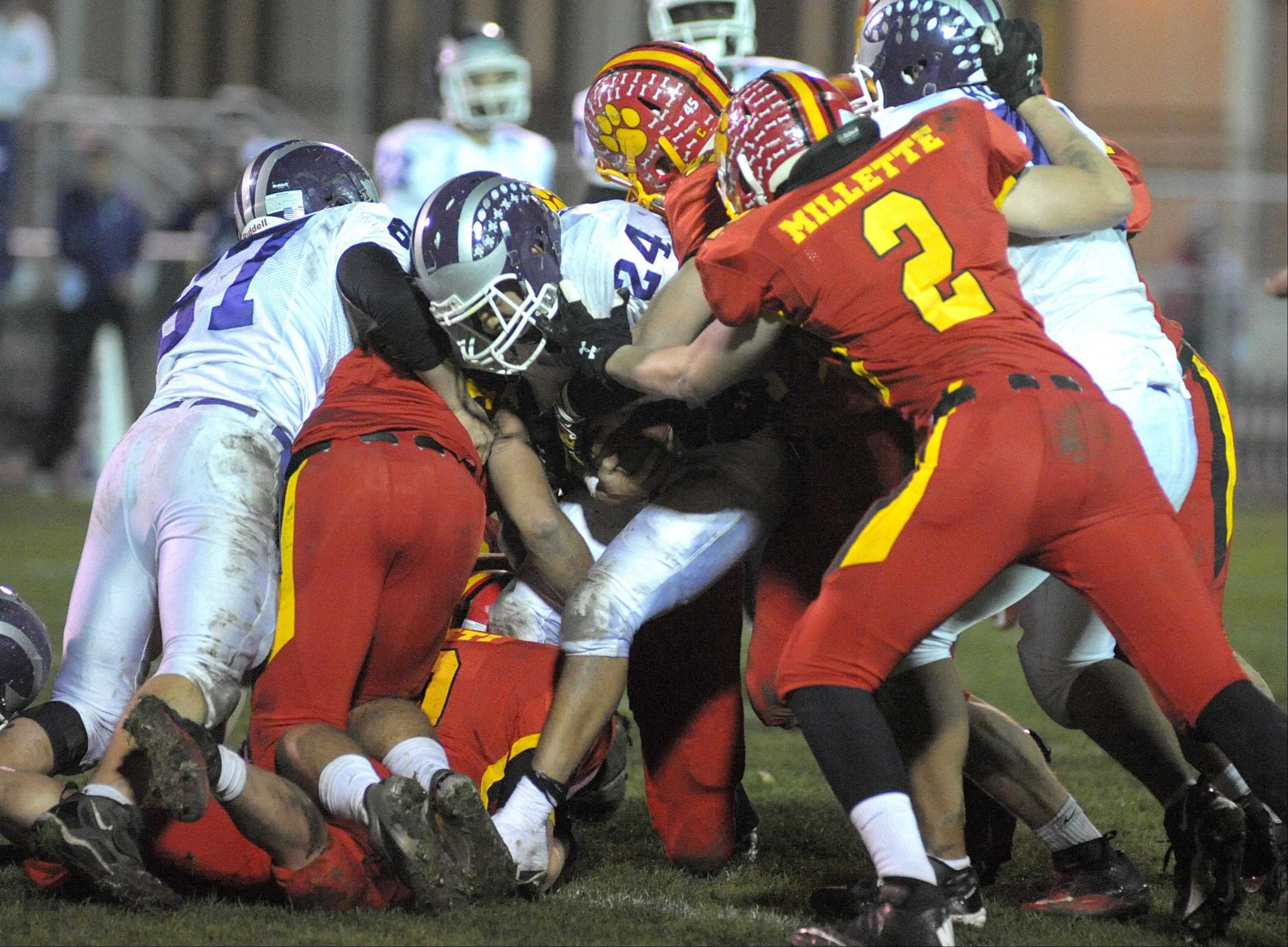Downers Grove North's Brandon Salter is taken down by a pack of Bulldogs in the fourth quarter of playoff game on Friday, October 26.