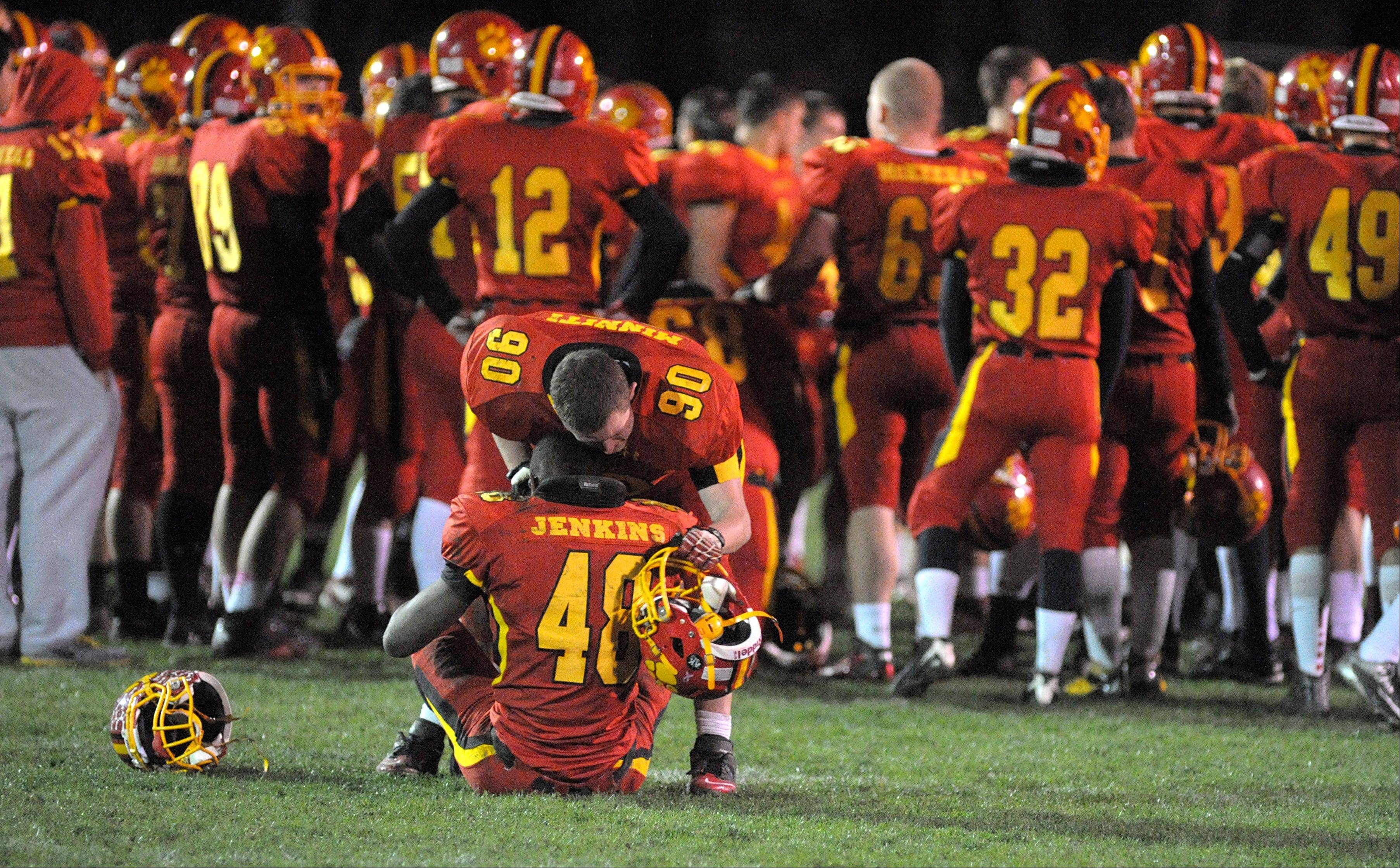 Batavia's Ryan Minniti comforts teammate Marquise Jenkins after their playoff loss to Downers Grove North on Friday, October 26.