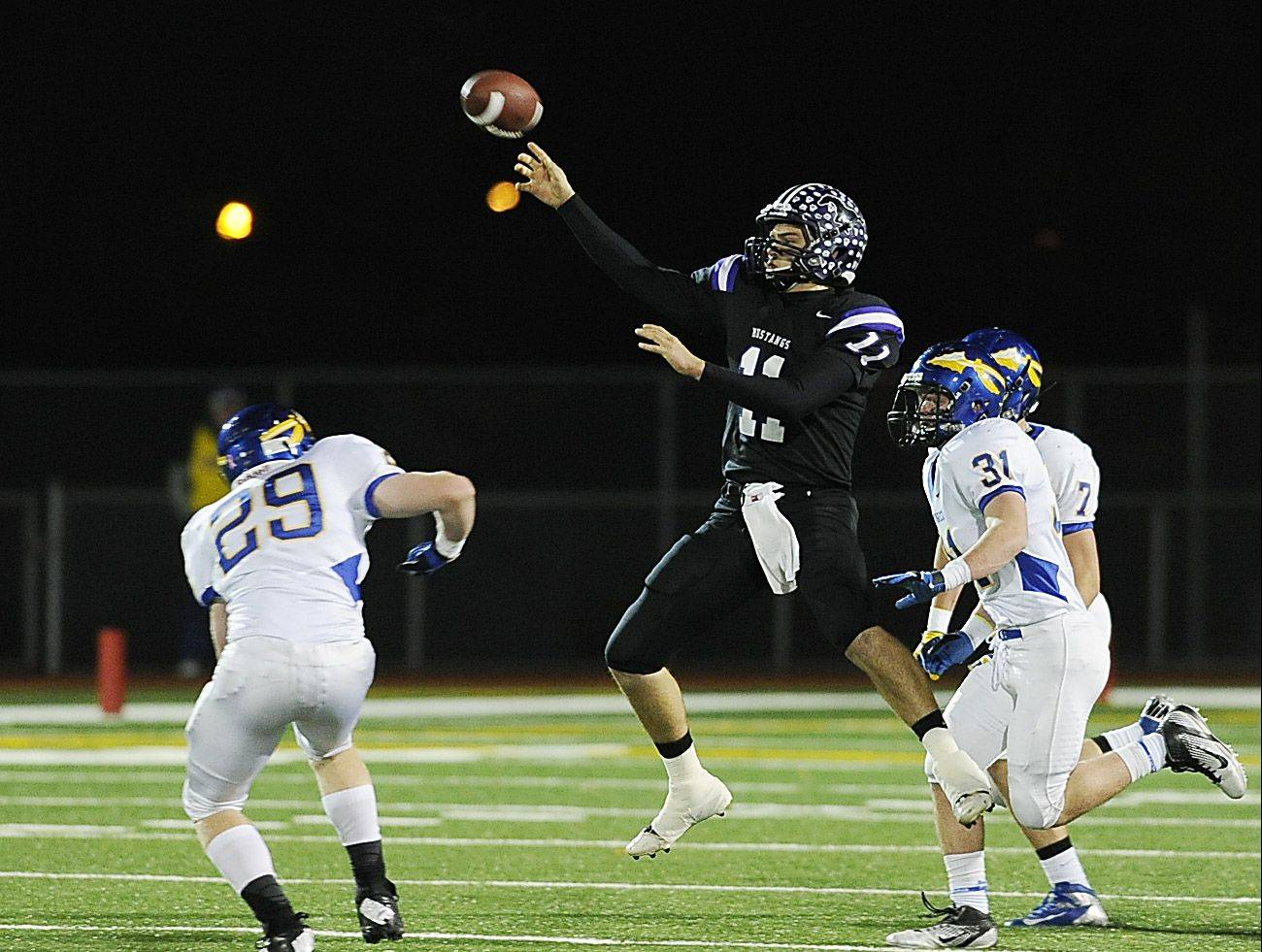 Rolling Meadows' Jack Milas lofts a pass from mid-air to Alex Niecikowski for a 64-yard completion in Class 6A first-round playoff action Friday at Meadows.