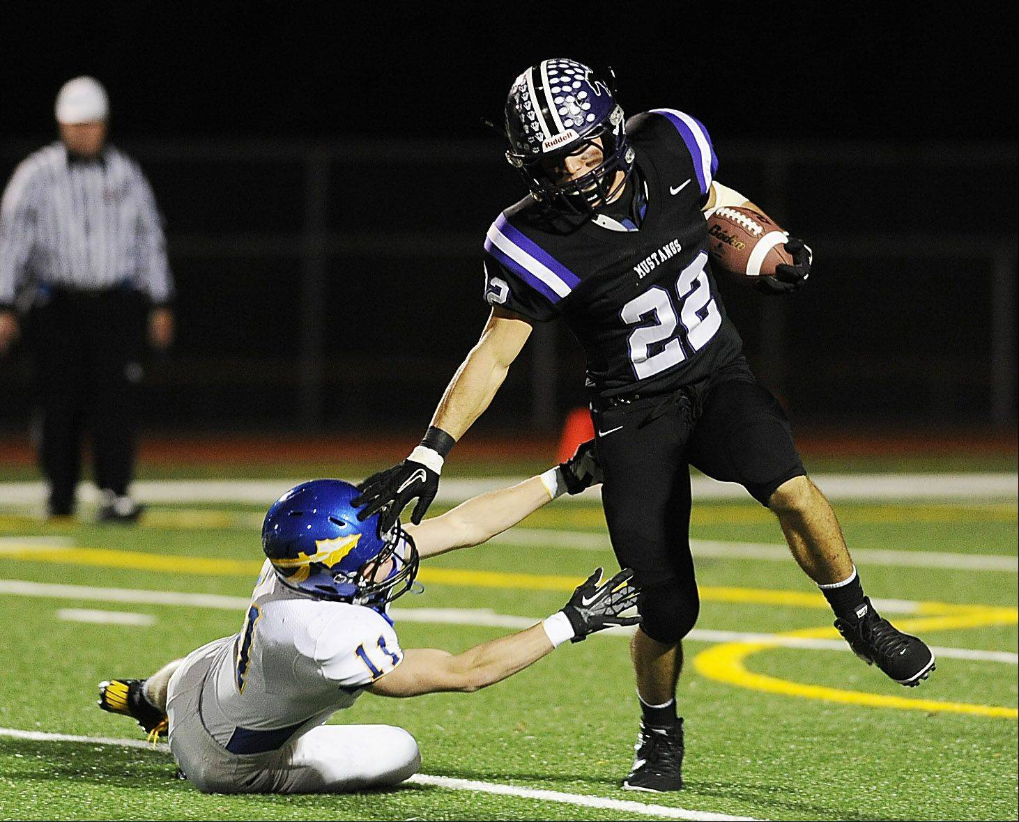 Mark Welsh/mwelsh@dailyherald.com Rolling Meadow's Austin Reed fends off Lake Forest's Andy Nelson in the first quarter in the Class 6A playoff football game at Rolling Meadows High School on Friday.