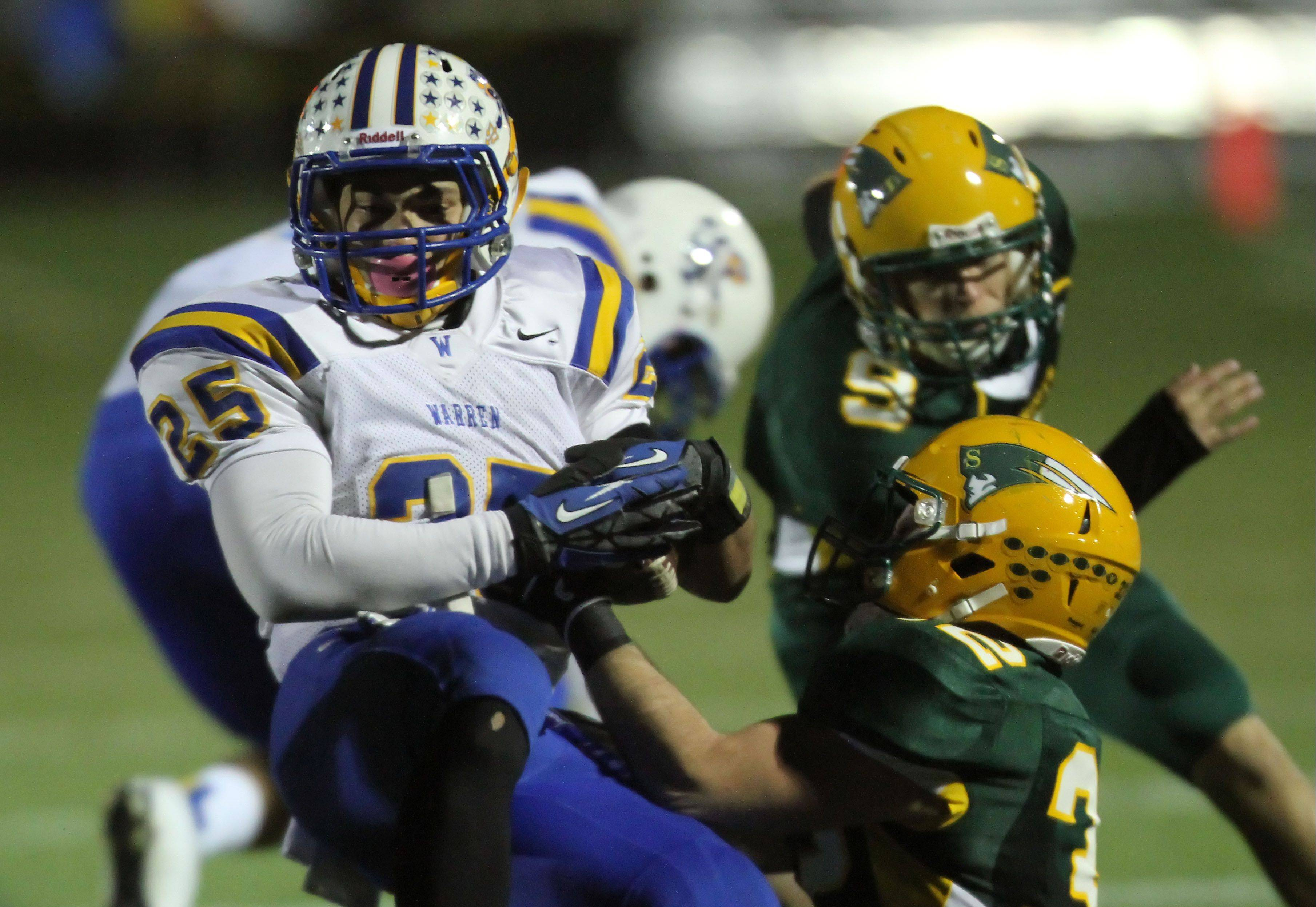 Warren's Davonte Willcox, left, tries to get around Stevenson's Ian Burns during round one of the Class 8A football playoffs Friday night at Stevenson.