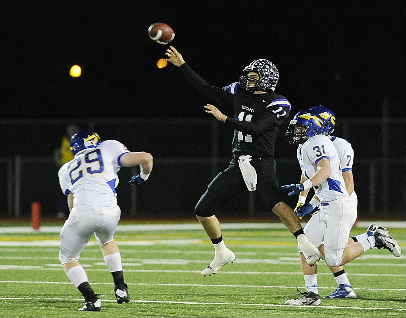 Rolling Meadow's Jack Milas throws on the run and in mid-air to Alex Niecikowski for a 64-yard pass play in the first quarter in the Class 6A playoff football game at Rolling Meadows High School on Friday.