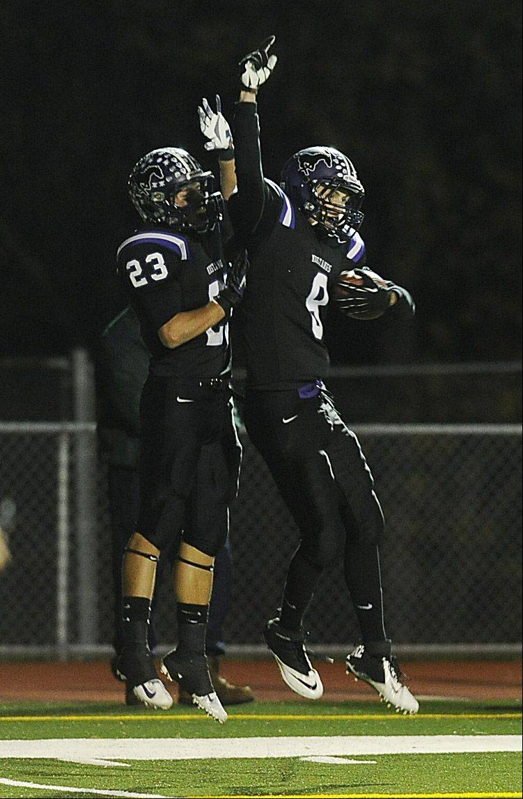 Rolling Meadow's James Grier celebrates his touchdown in the first quarter with teammate Austin Reed against Lake Forest in the Class 6A playoff football game at Rolling Meadows High School on Friday.