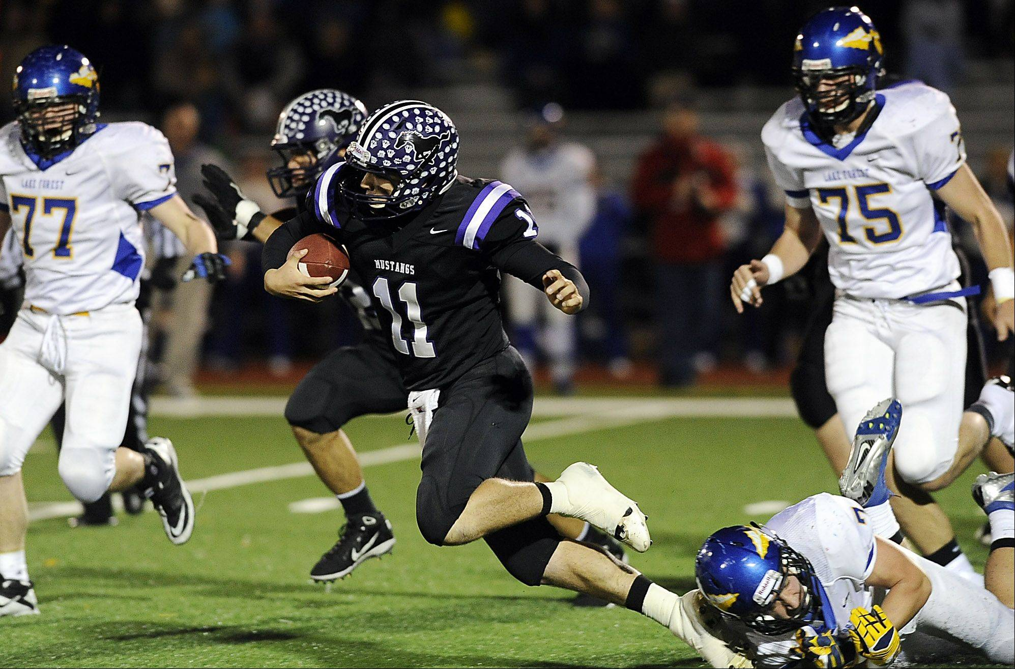 Rolling Meadow's Jack Milas runs for yardage but is tripped up by Lake Forest's Thomas Kutschke in the first quarter in the Class 6A playoff football game at Rolling Meadows High School on Friday.