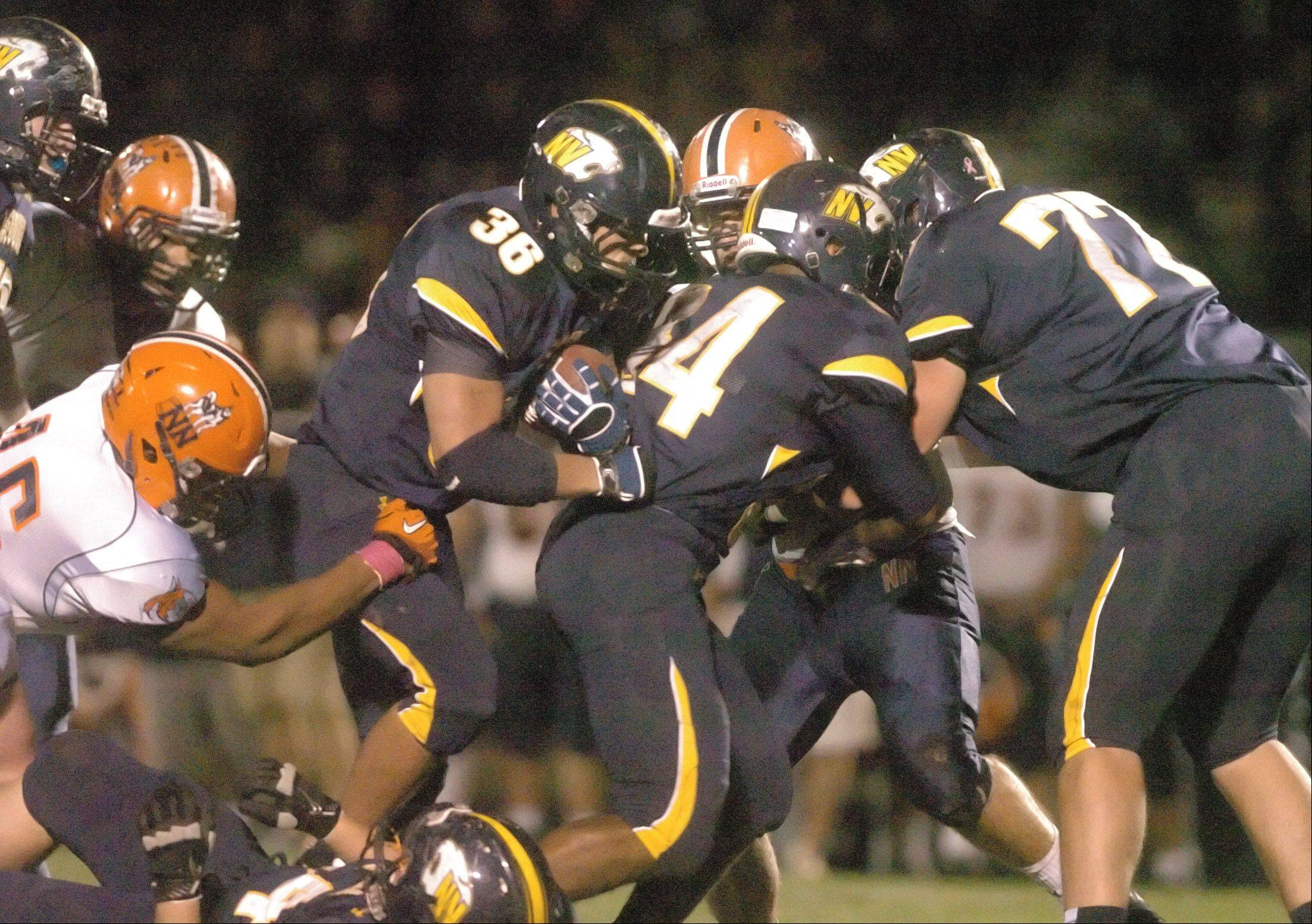 Joey Rhattigan of Neuqua,center, moves the ball during the Naperville North at Neuqua Valley football game Friday.