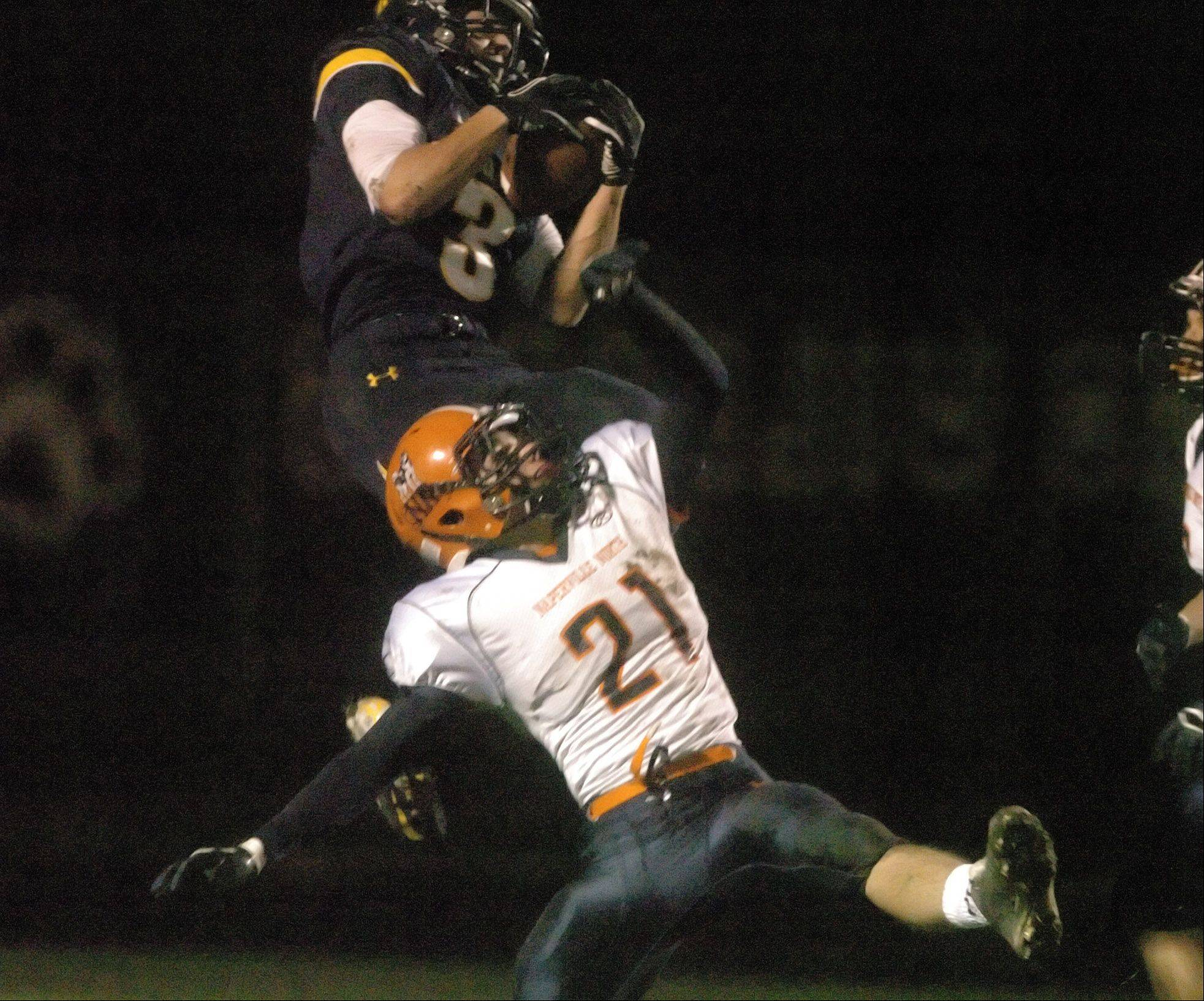 Mikey Dudek of Neuqua pulls down a pass while Danny Schertz of Naperville North tries to stop him.