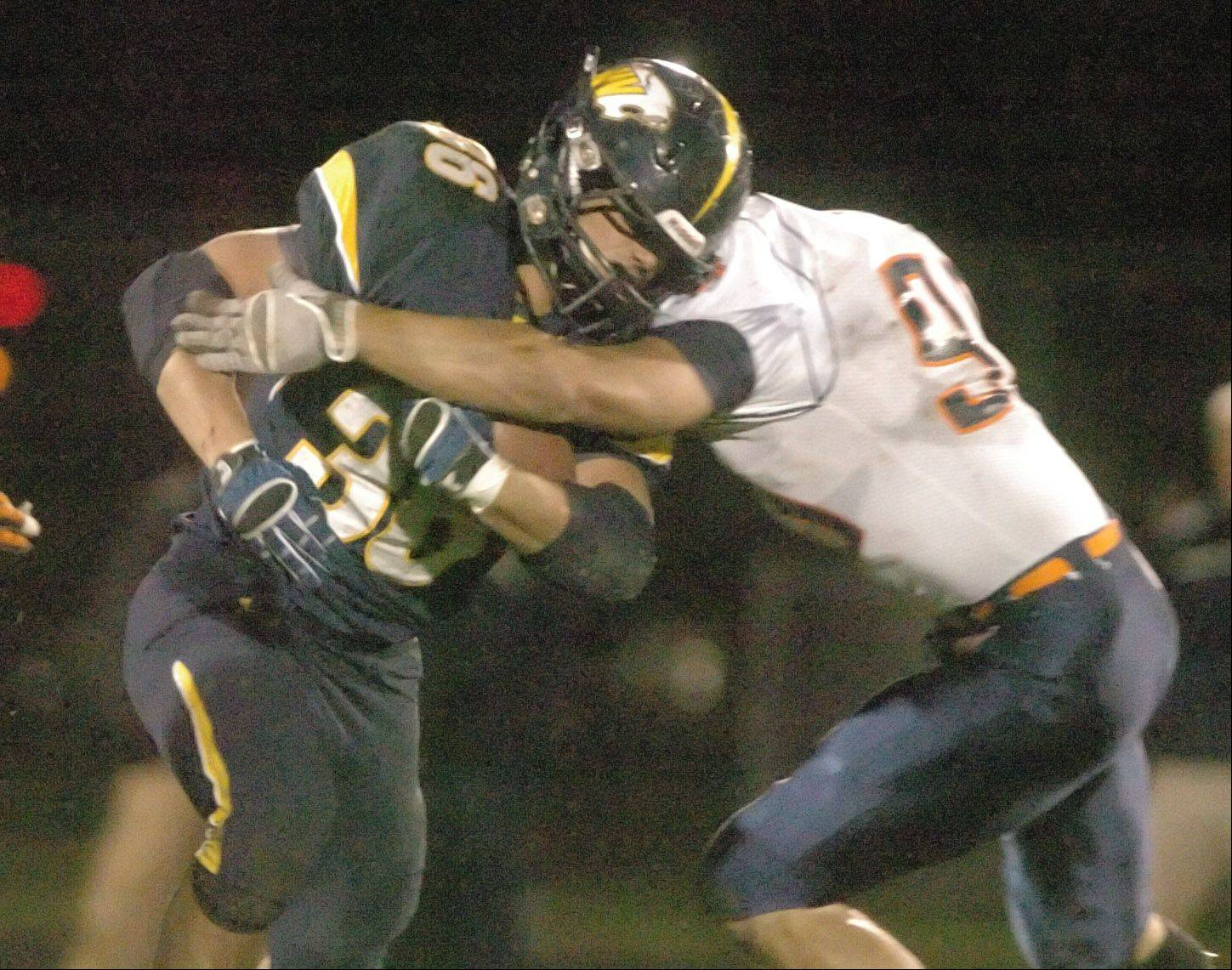 Joey Rhattigan moves the ball around a Naperville North defender during the Naperville North at Neuqua Valley football game Friday.