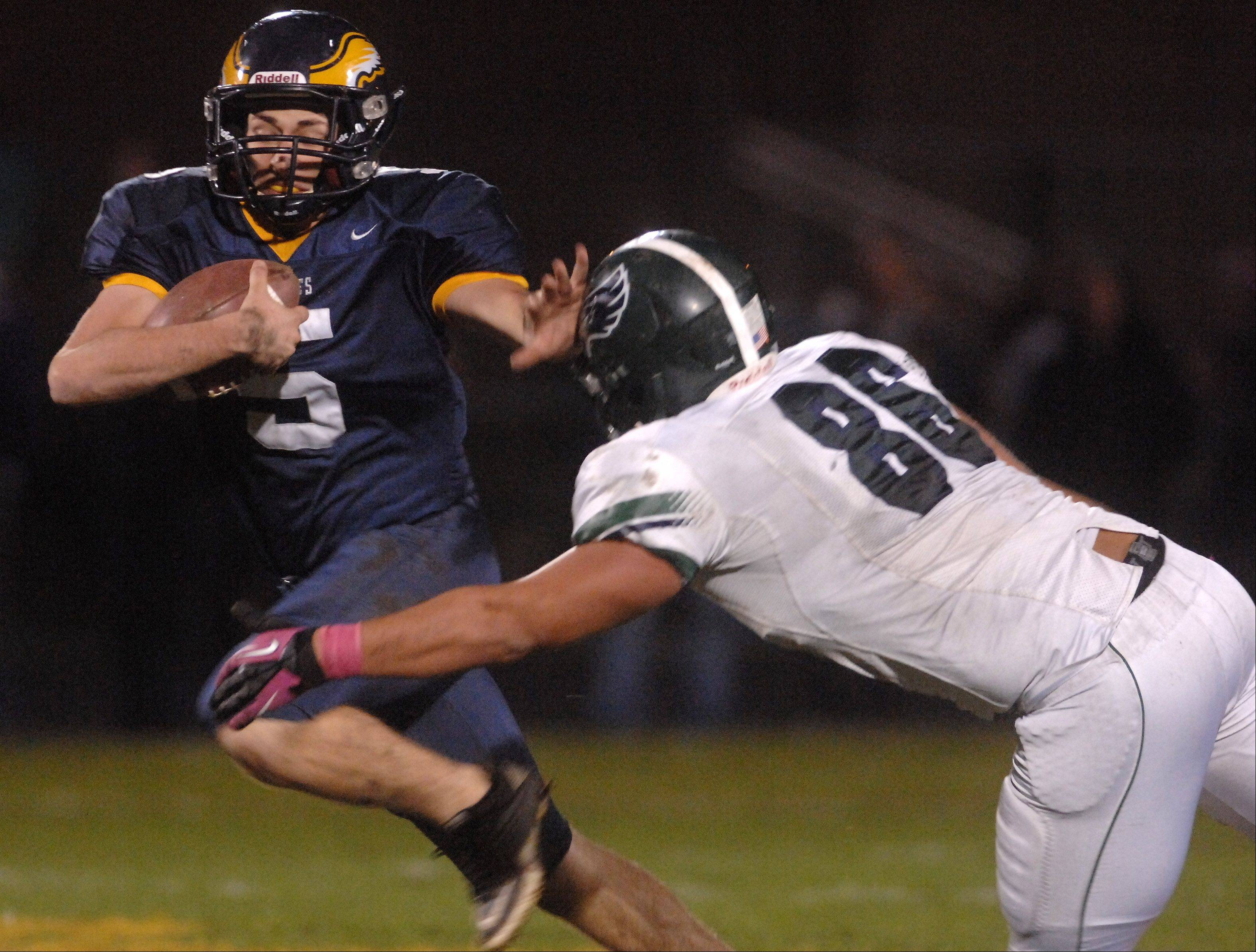 Leyden's Mike Smith (5) gives the stiff arm to Bartlett's Chris Kantzavelos (86) during Friday's game.
