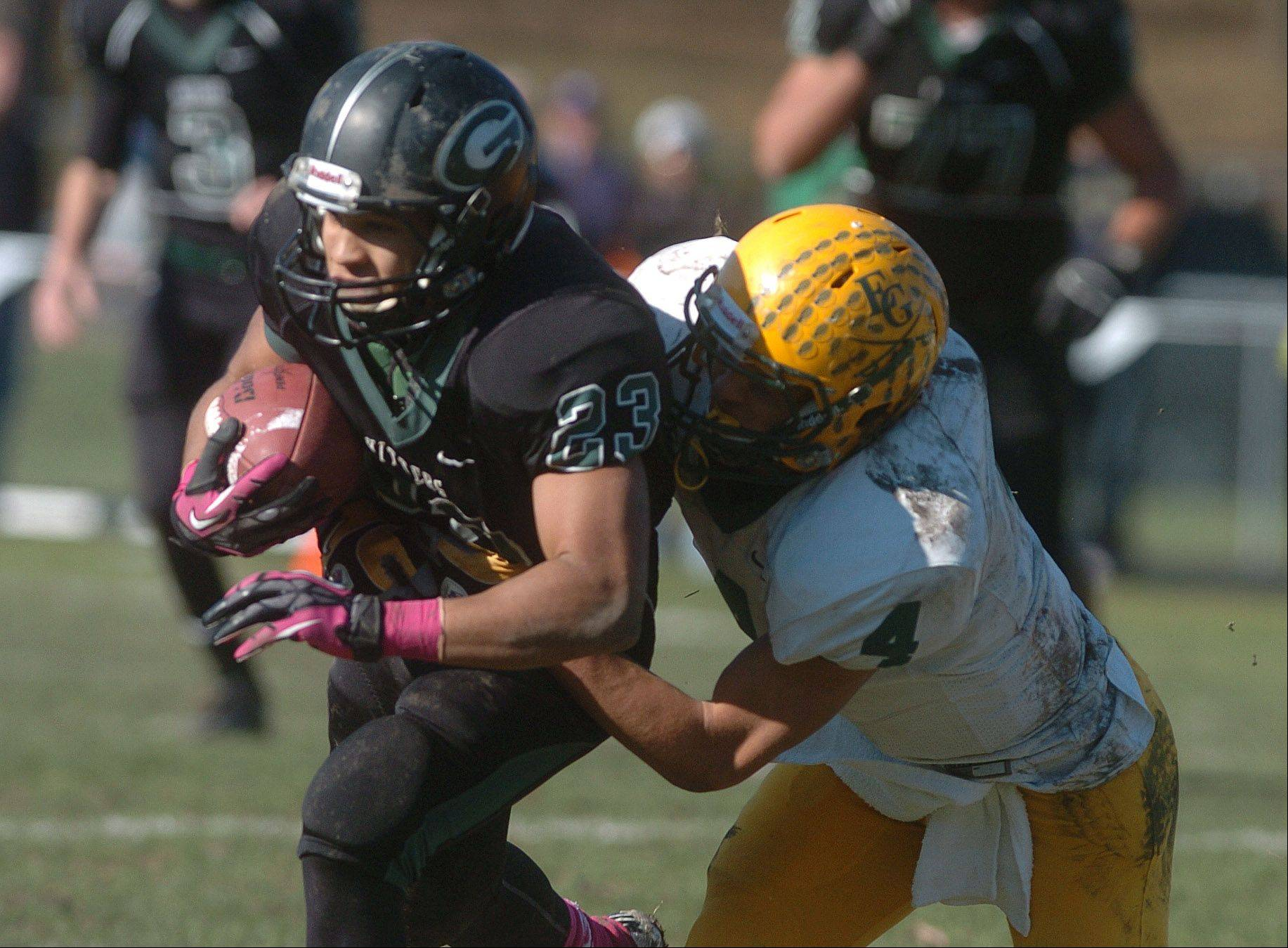 Scott Andrews of Glenbard West is trailed by Mike Bishoff of Elk Grove during the Elk Grove at Glenbard West football game Saturday.