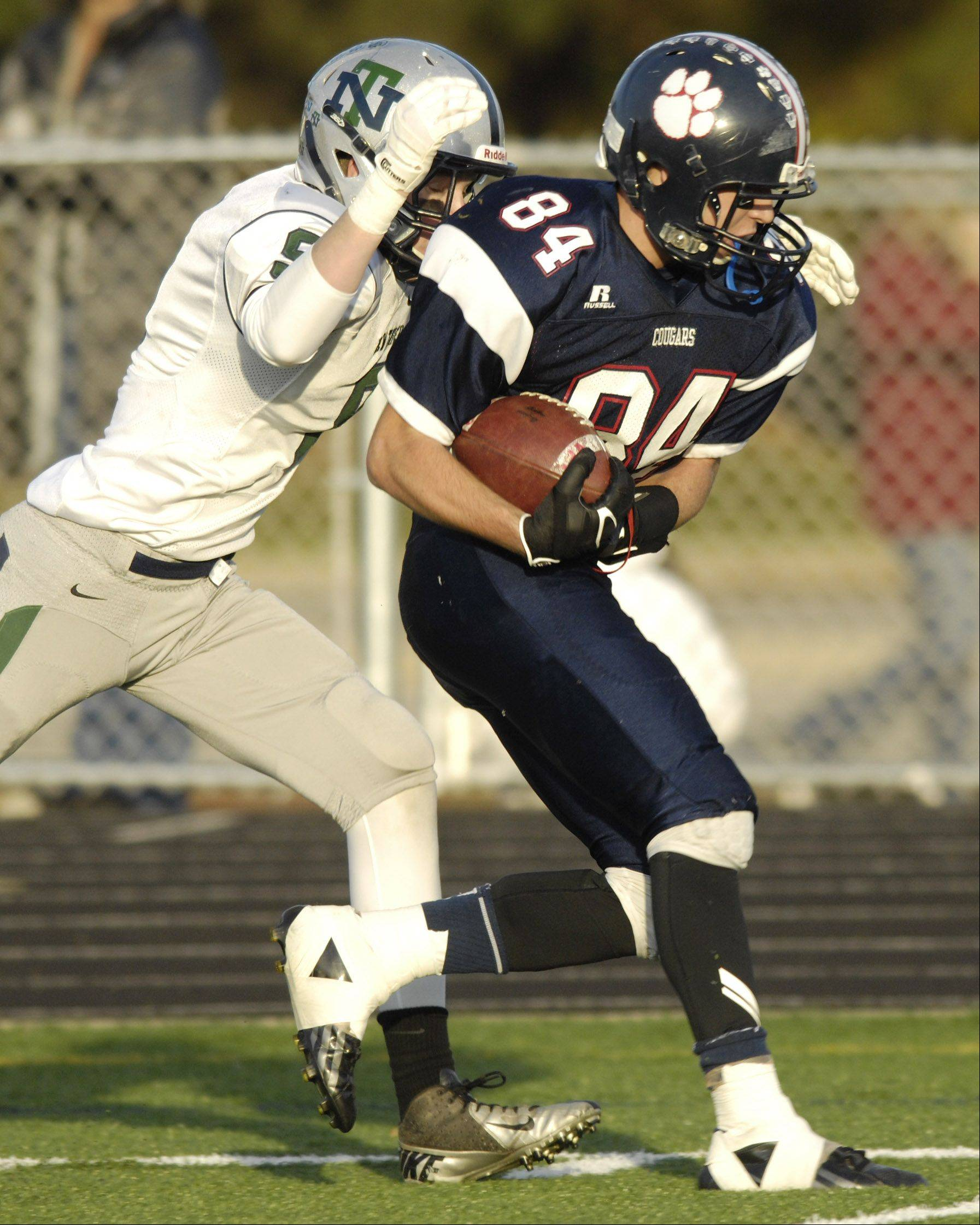 Conant's Tim Manczko, right, makes a catch for a big gain in front of New Trier's Trent Peters during Saturday's game.