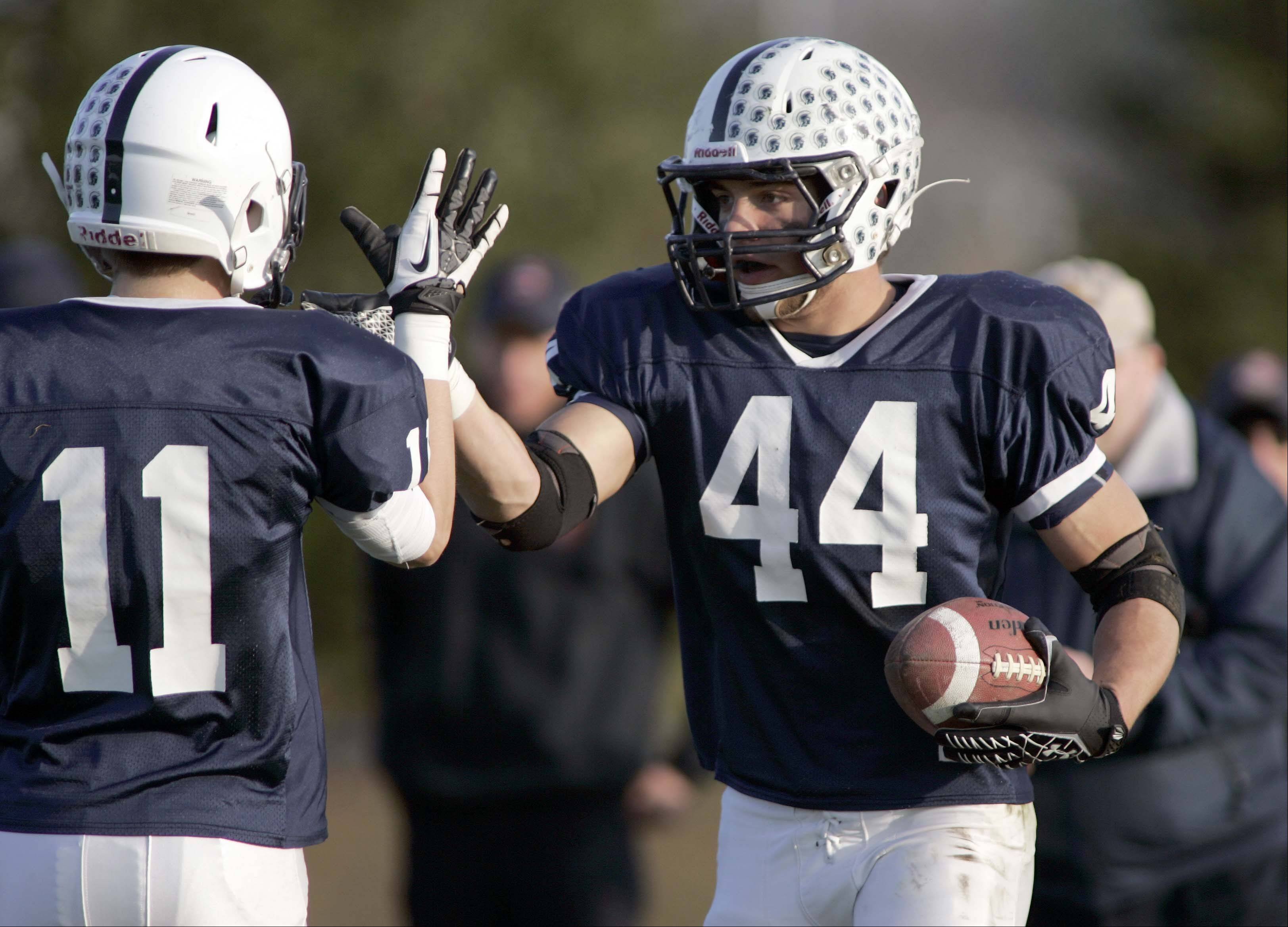 Cary-Grove's Kyle Norberg (44) is greeted by teammate Patrick Snell after scoring one of his touchdowns during the Trojans' 41-7 Class 6A playoff win over Rockford Auburn in Cary Saturday.