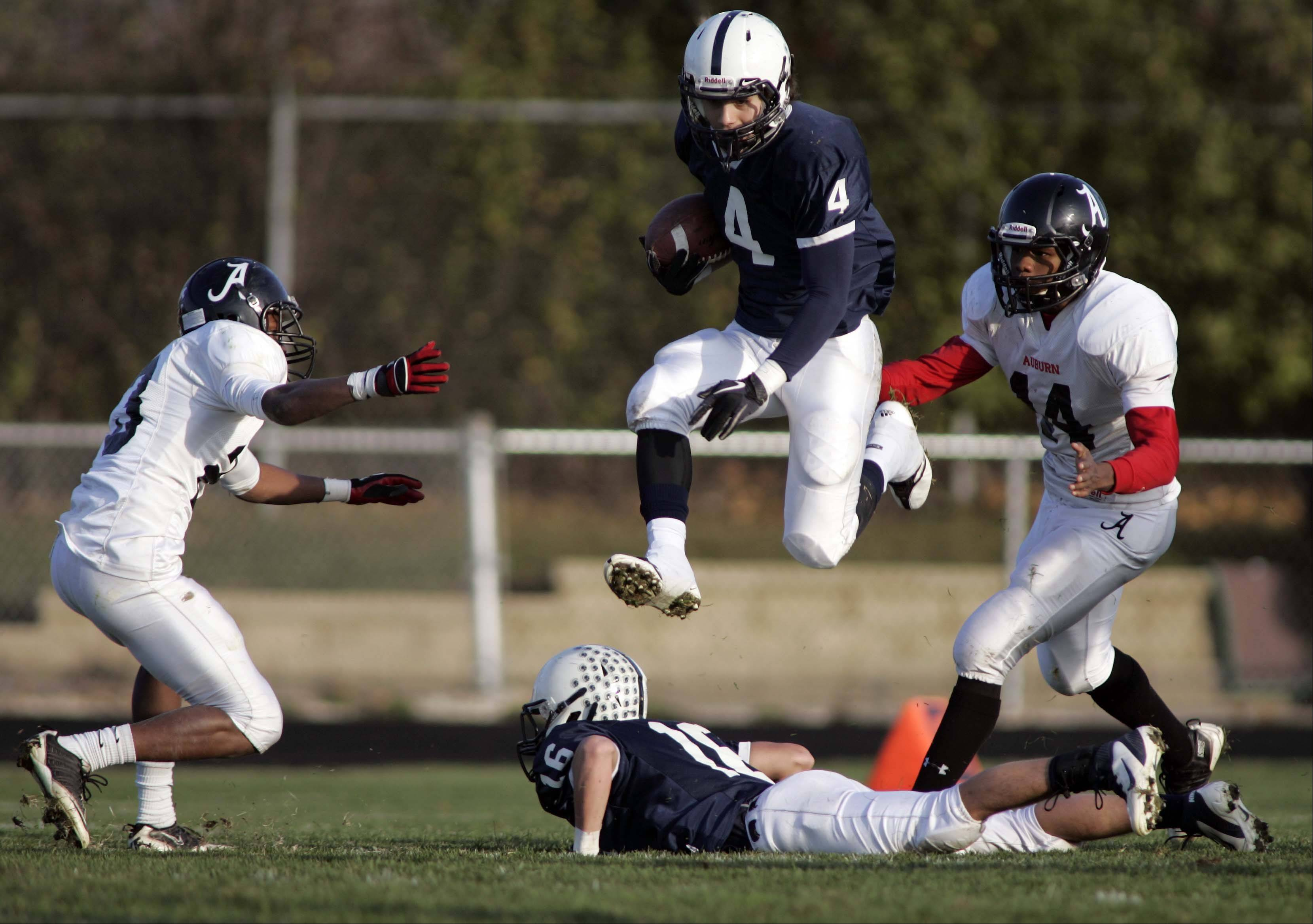 Cary-Grove's Ryan Mahoney (4) leaps over Kaene Connington to get some more running room during Cary-Grove's Class 6A playoff with over Rockford Auburn Saturday in Cary.