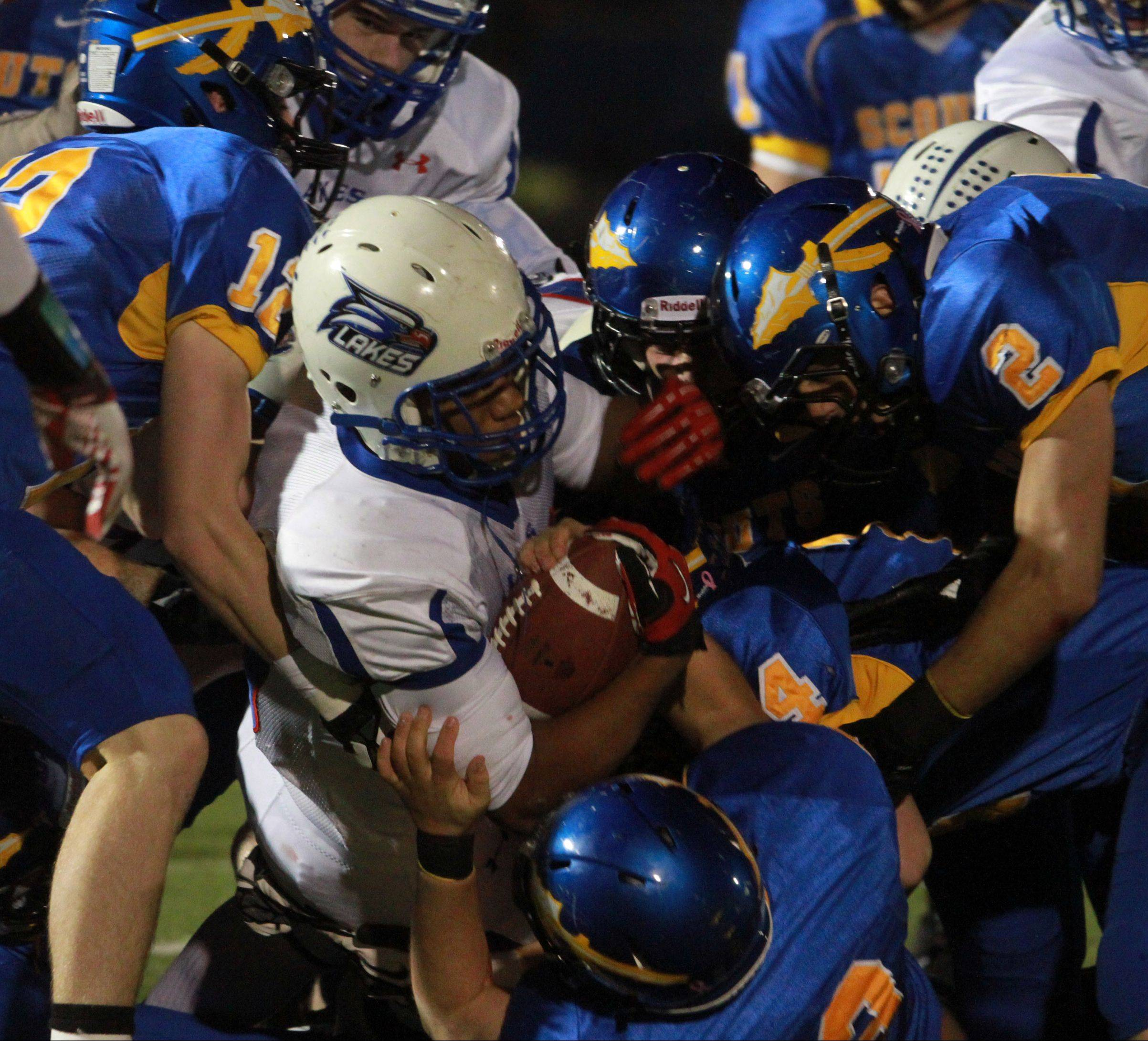 Lakes running-back Direll Clark is pulled down by a host of Lake Forest defenders Friday night in round two of the Class 6A playoffs in Lake Forest.