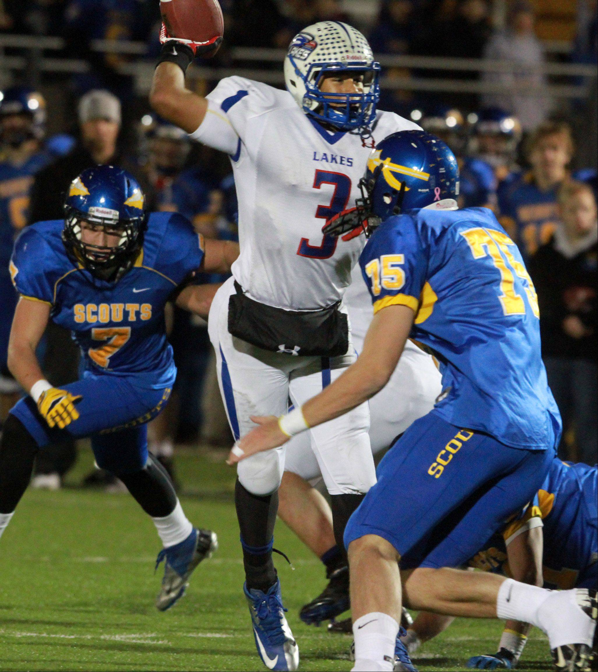Lakes quarterback passes under rush by two Lake Forest defenders at Lake Forest in round two of Class 6A state playoffs on Friday, Nov. 2.