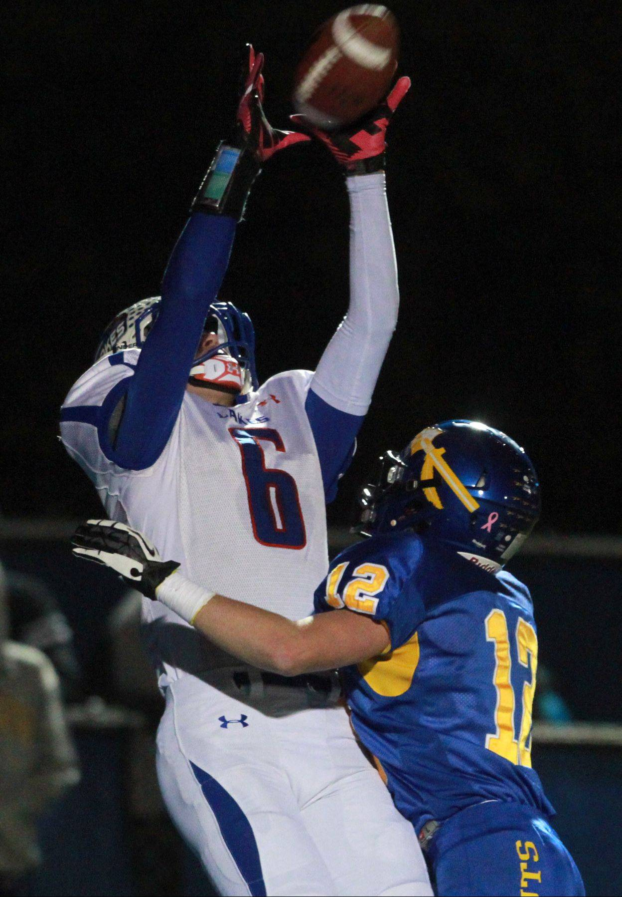Lakes' Justin Bergeron pulls in a first-quarter touchdown pass above Lake Forest defender Alexander Moore in round two of Class 6A playoffs Friday in Lake Forest.