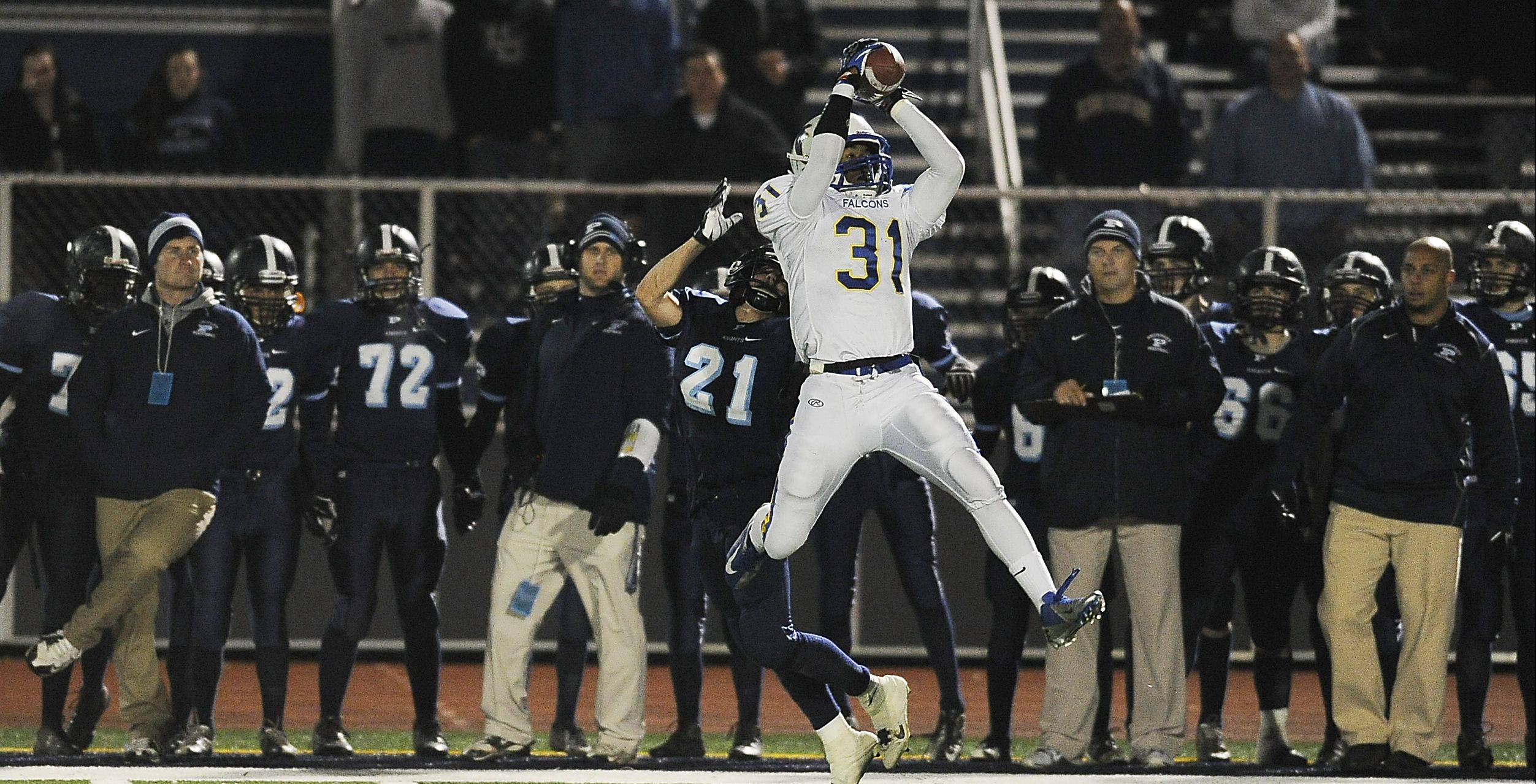 Wheaton North's Jaylen Howze leaps for an interception in front of Prospect's Joe Gleason in the fourth quarter on Friday night in Mt. Prospect.