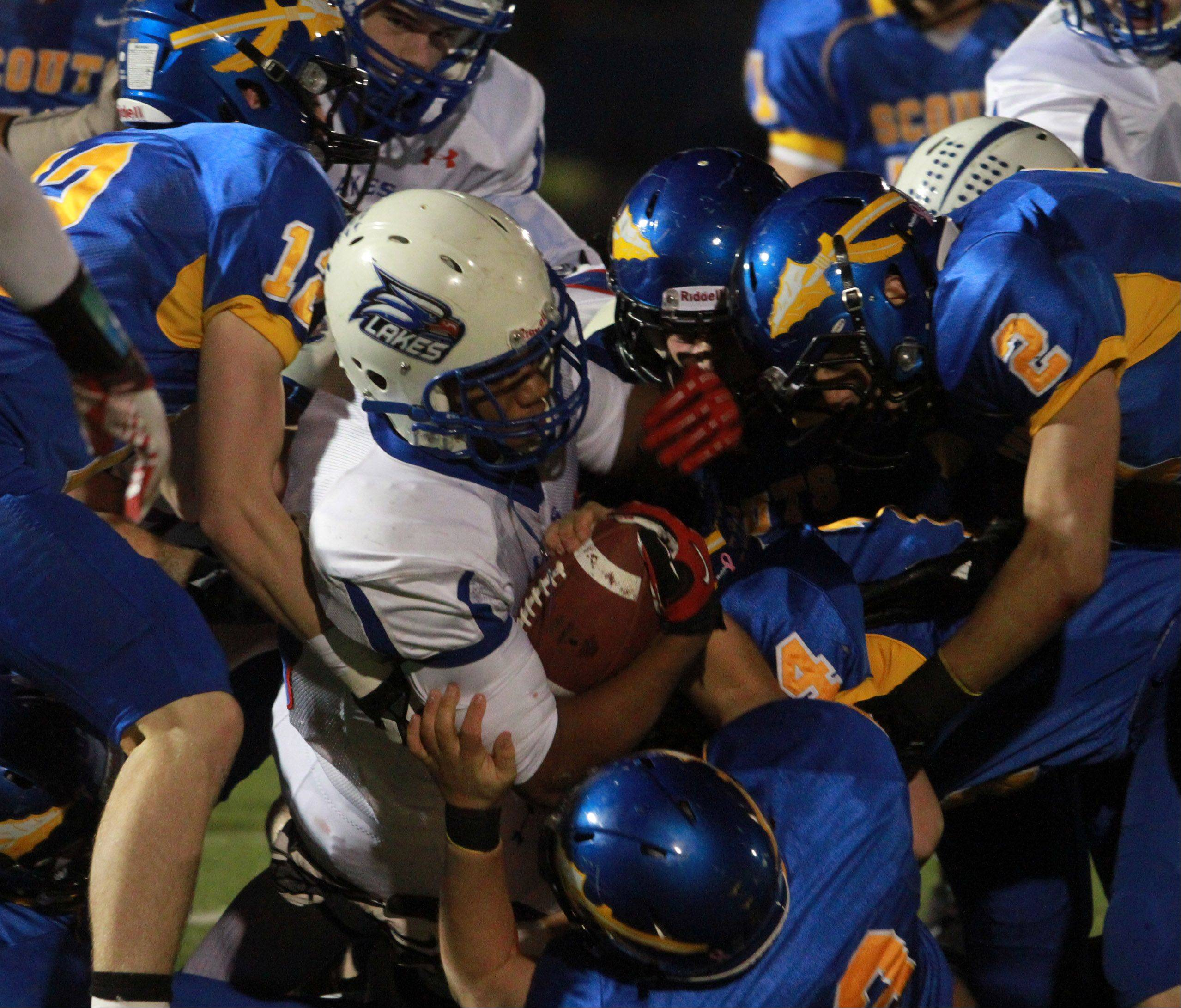 Lakes running-back Direll Clark is pulled down by a host of Lake Forest defenders.
