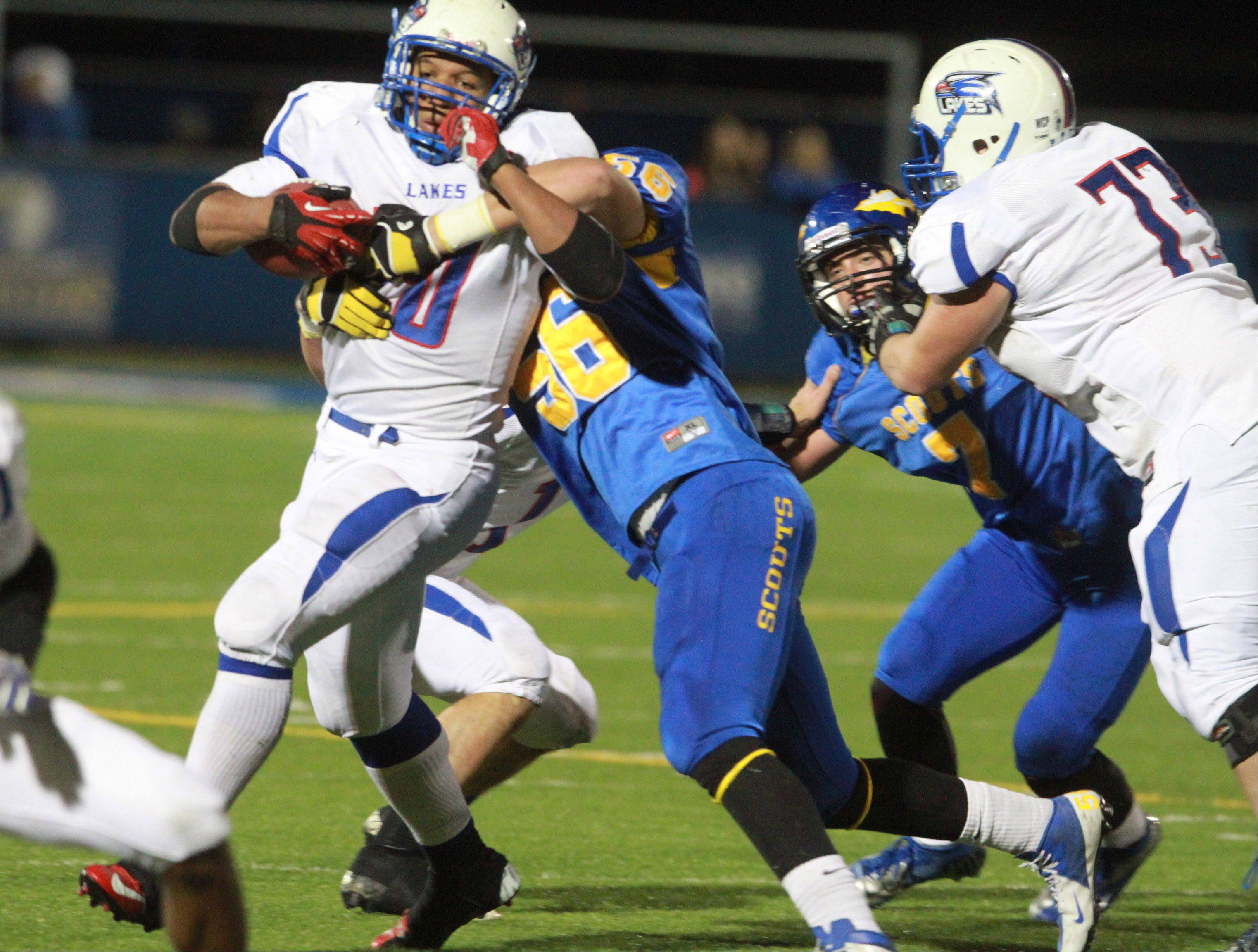 Lakes running-back Direll Clark is wrapped up by a Lake Forest defender.
