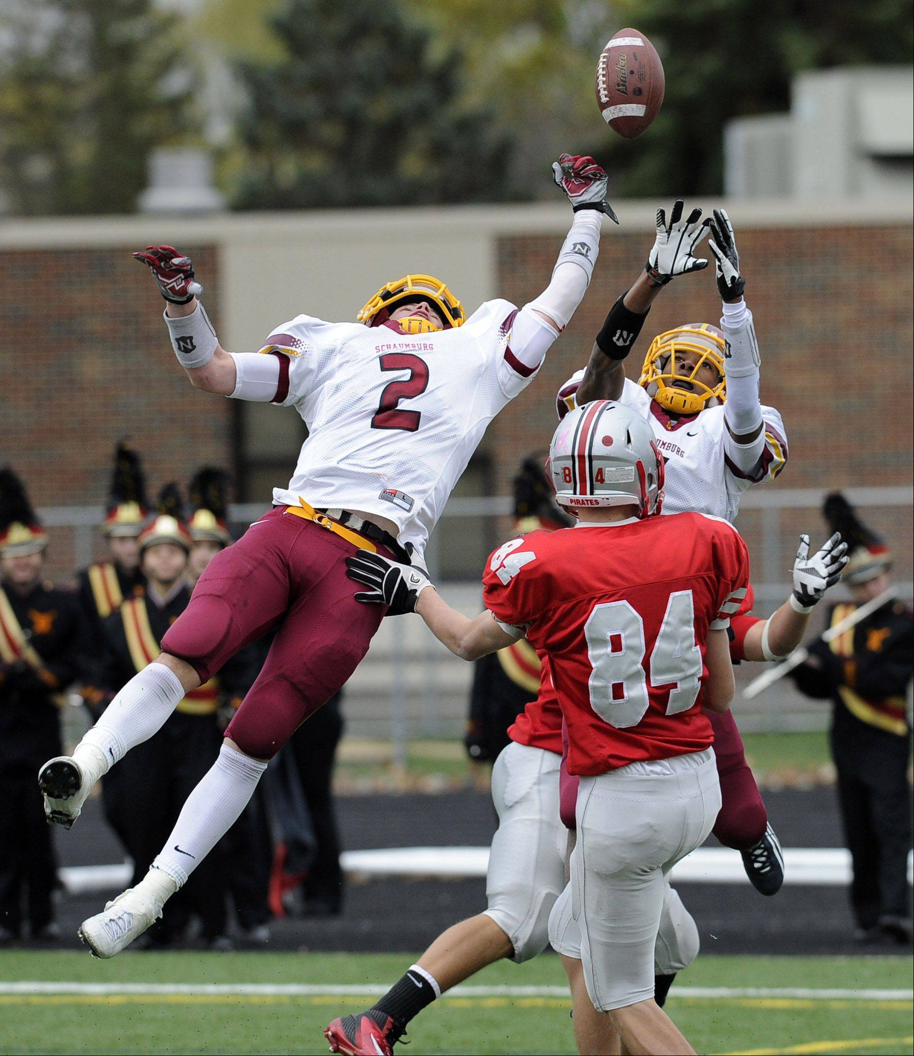 In a Hail-Mary pass thrown late in the second quarter by Palatine, Schaumburg's Cole Reyes tips the ball and it is nearly caught by Palatine's Jesse Bobbit but it hit the ground first in Palatine's victory over Schaumburg in the Class 8A playoffs at Palatine High School on Saturday.