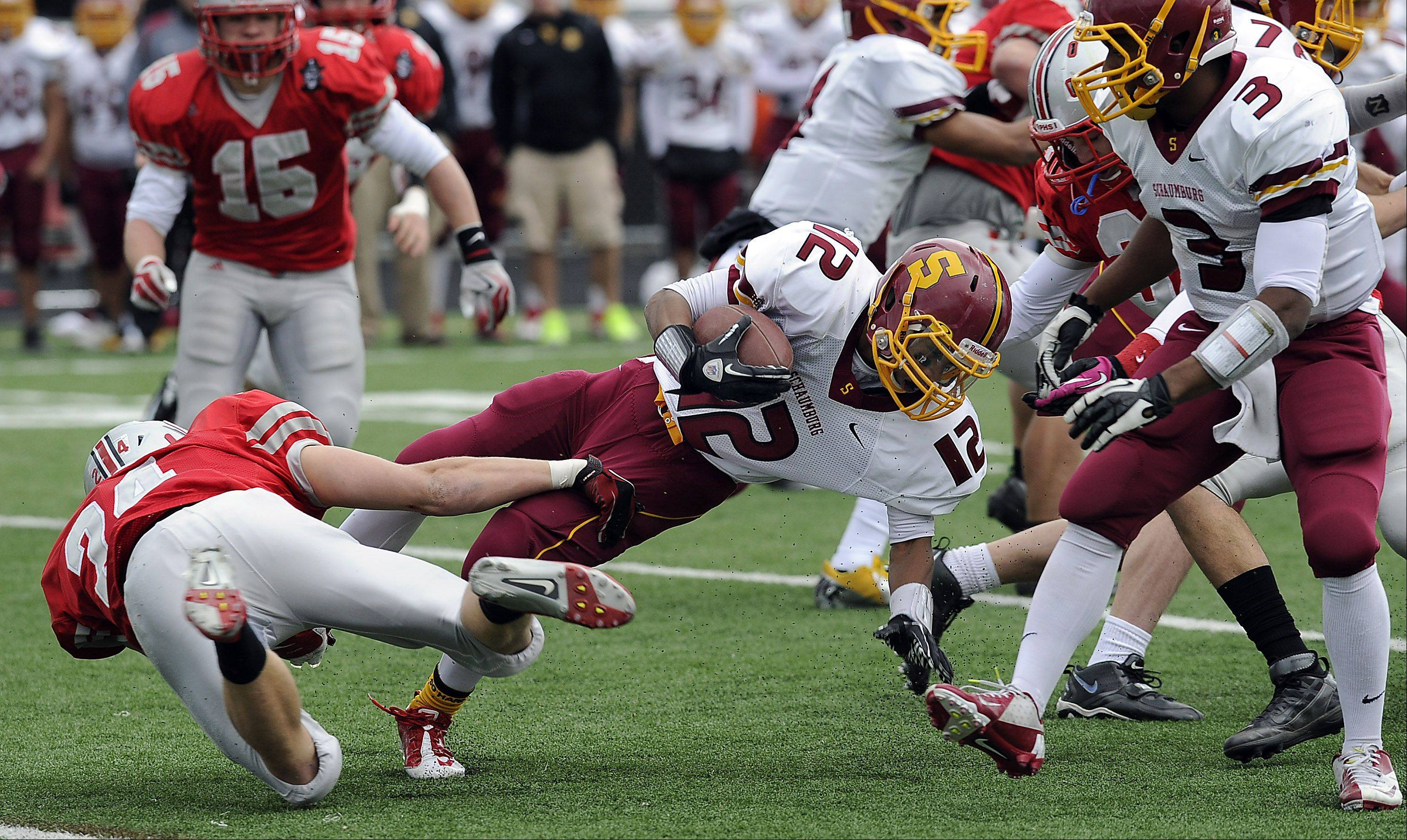 Palatine's Dan Riddle shows remarkable defensive skills on stopping Schaumburg's Stacey Smith behind the line of scrimmage in the Class 8A playoffs at Palatine High School on Saturday.