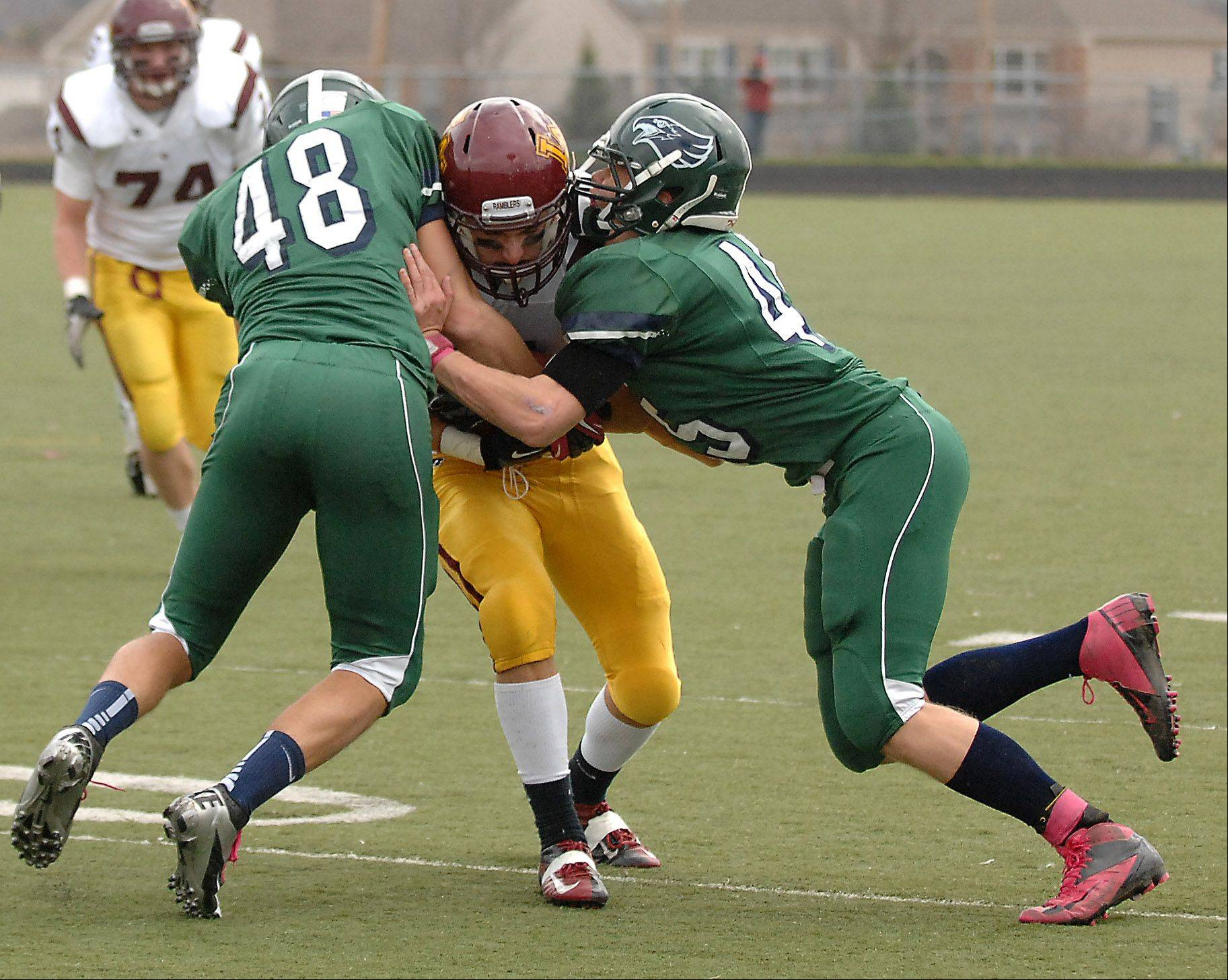 Bartlett's Nick Andreucetti, left, and Chris Janssen combine to tackle Loyola Academy receiver Joe Joyce during Saturday's 8A playoff game at Millennium Field in Streamwood.