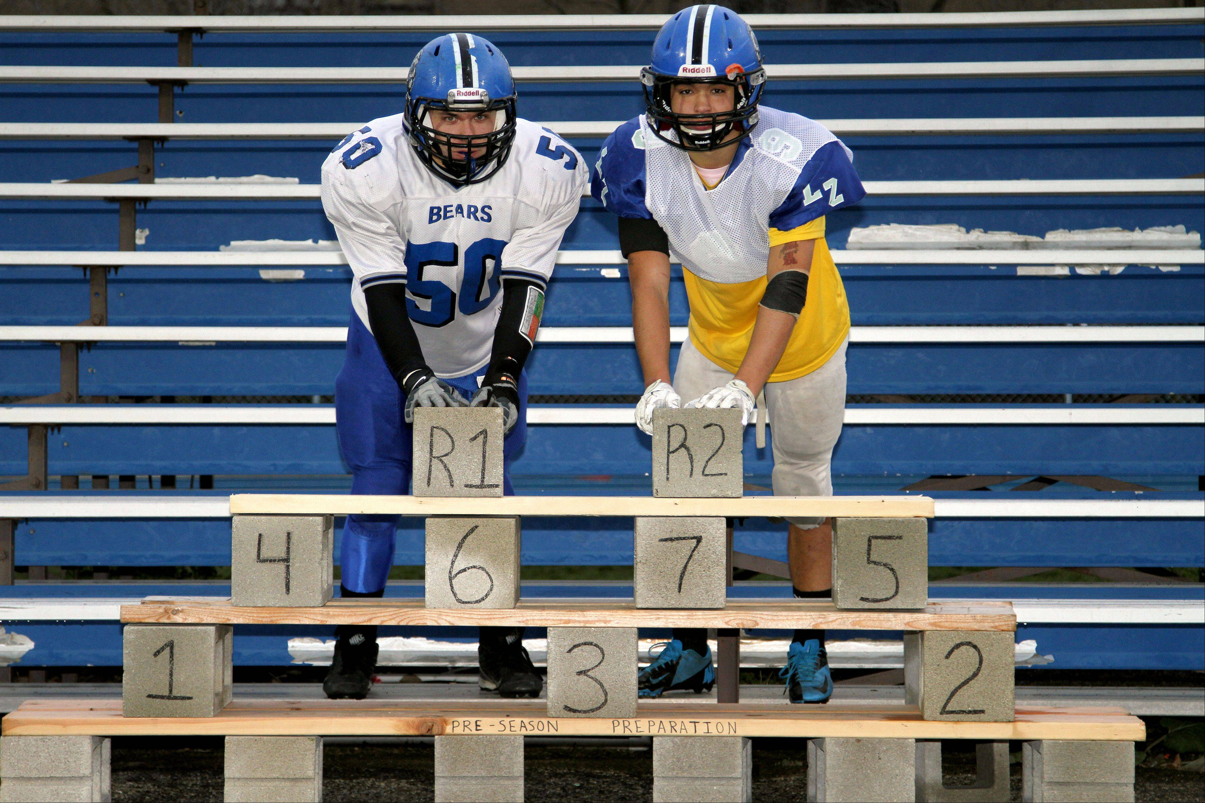 Lake Zurich football captains Jerry Bauer and Grant Soucy lean on a cinder block structure in the North end zone of the Bears' stadium. The cinder blocks symbolize the wins in the season, while each player gets his own individual brick in the structure.