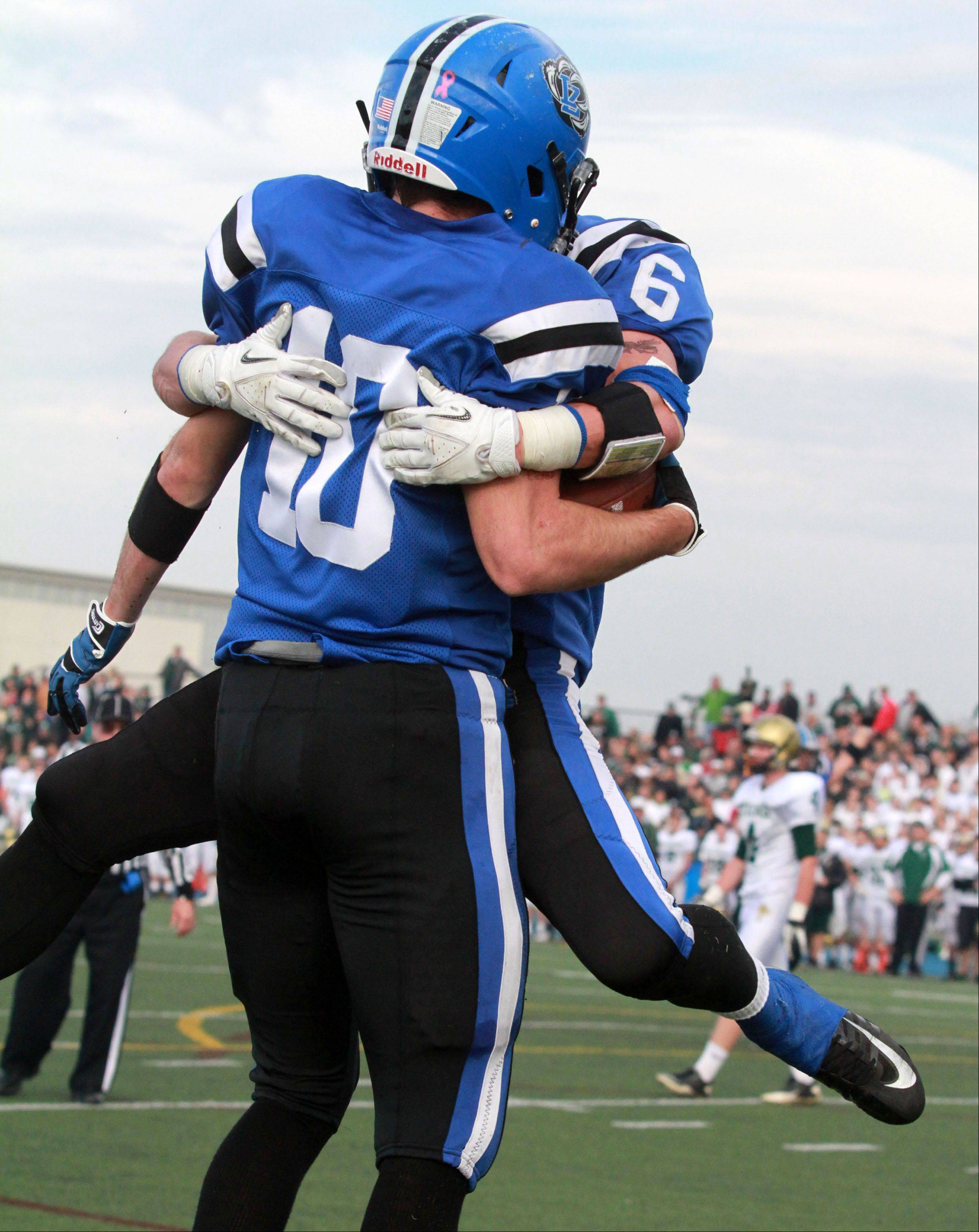 Lake Zurich's Sean Lynch leaps into the arms of Jake Stauner after Stauner caught a touchdown pass against Rockford Boylan in Class 7A state quarterfinal play at Lake Zurich on Saturday.