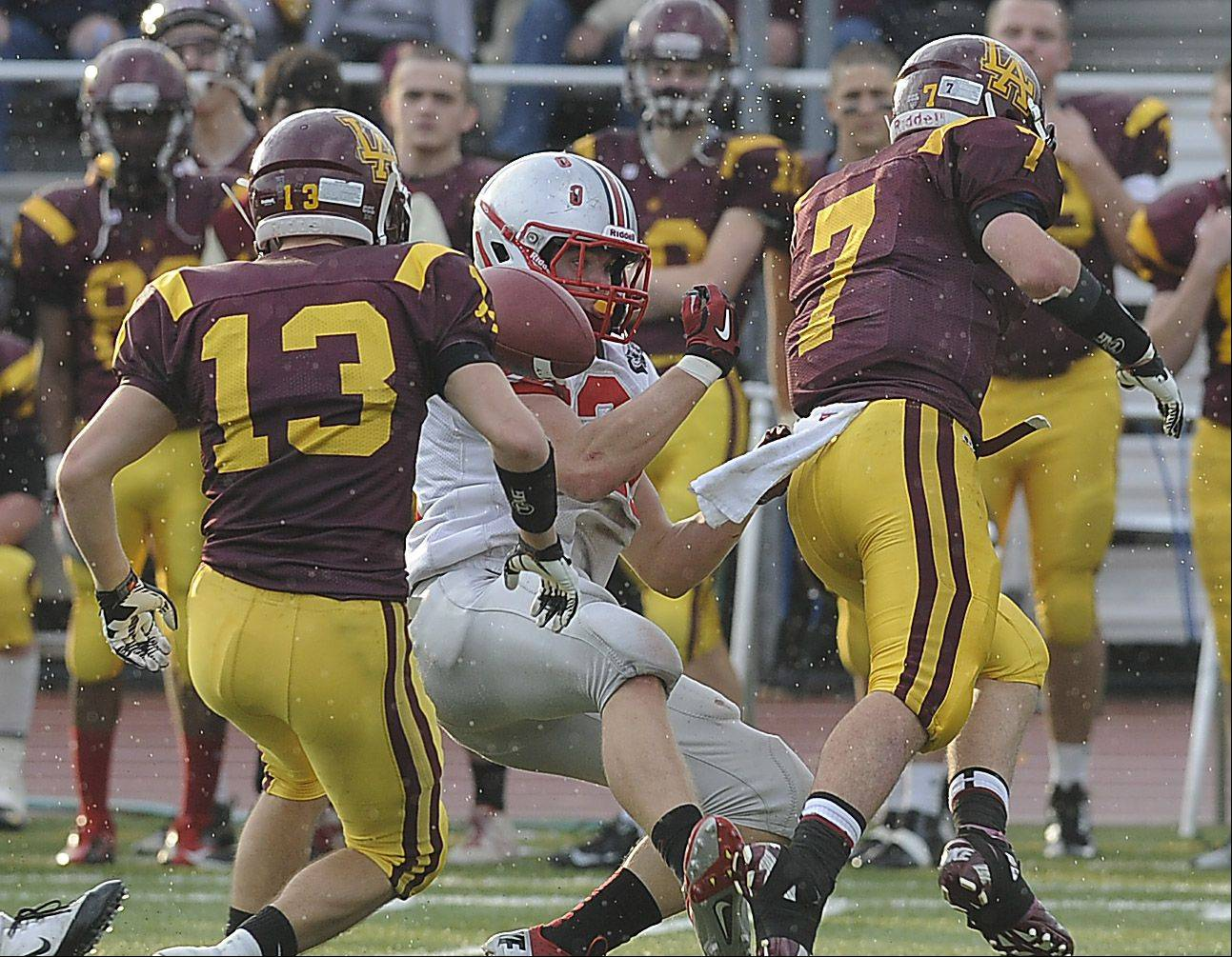 Palatine's Dan Riddle is hit on this broken-pass play by Loyola's Daniel Rafferty in the third quarter .
