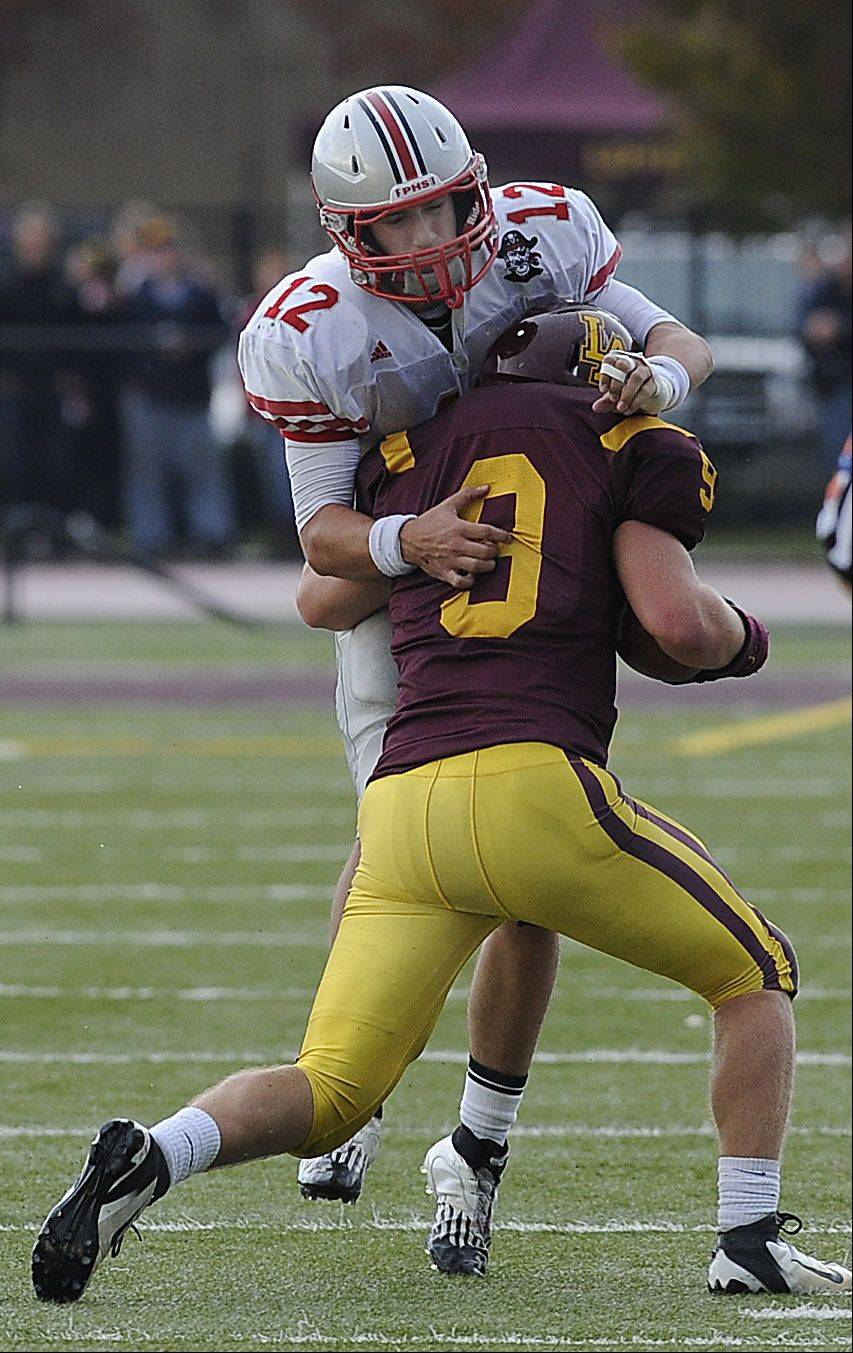 Palatine's quarterback Ethan Olles makes a tackle on Loyola's Cody Sullivan .