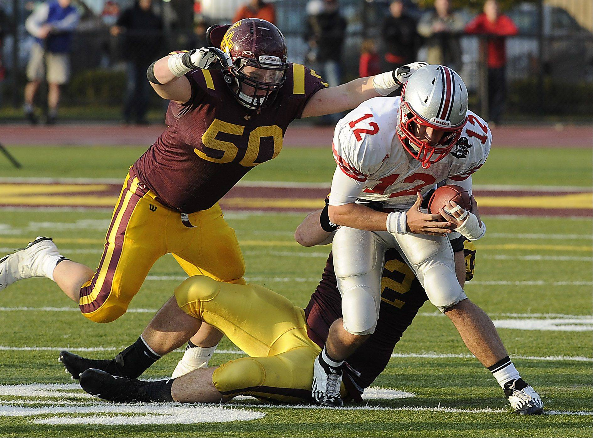 Loyola's John Rushin and Darby Goodwin sack Palatine quarterback Ethan Olles.