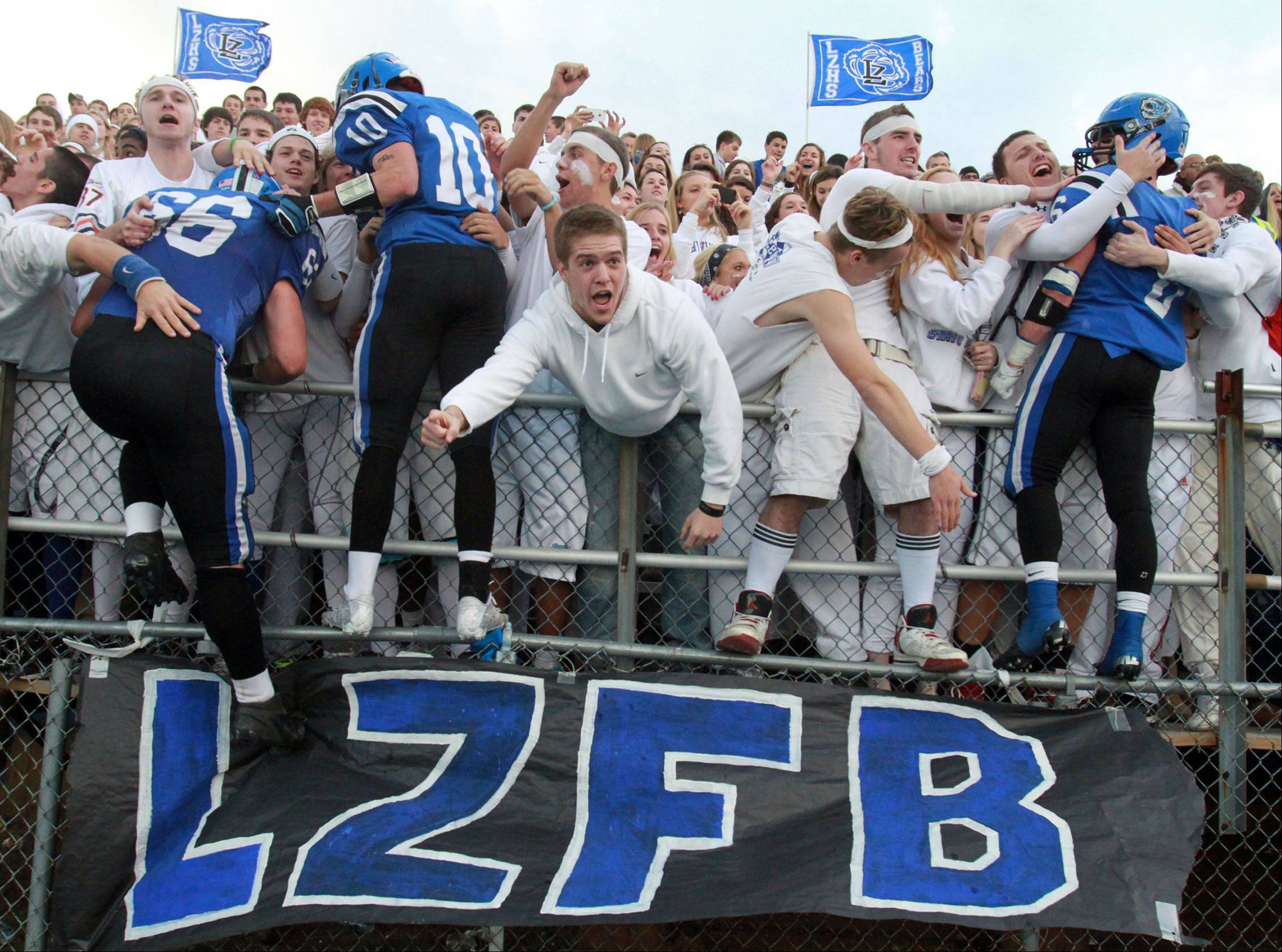 Lake Zurich players leap into the student fan section after winning over Rockford Boylan in Class 7A state quarterfinal game at Lake Zurich on Saturday.