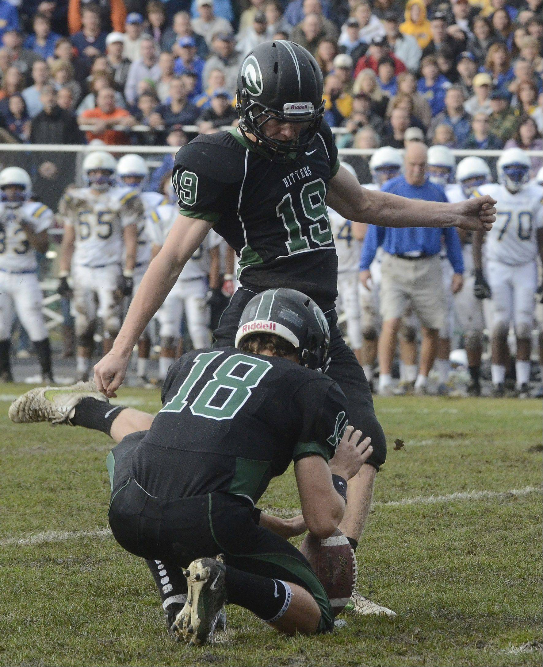Glenbard West's Hayden Lekacz kicks a field goal with Drew Vogg holding during the Hilltoppers' 3-0 win over Wheaton North Saturday.