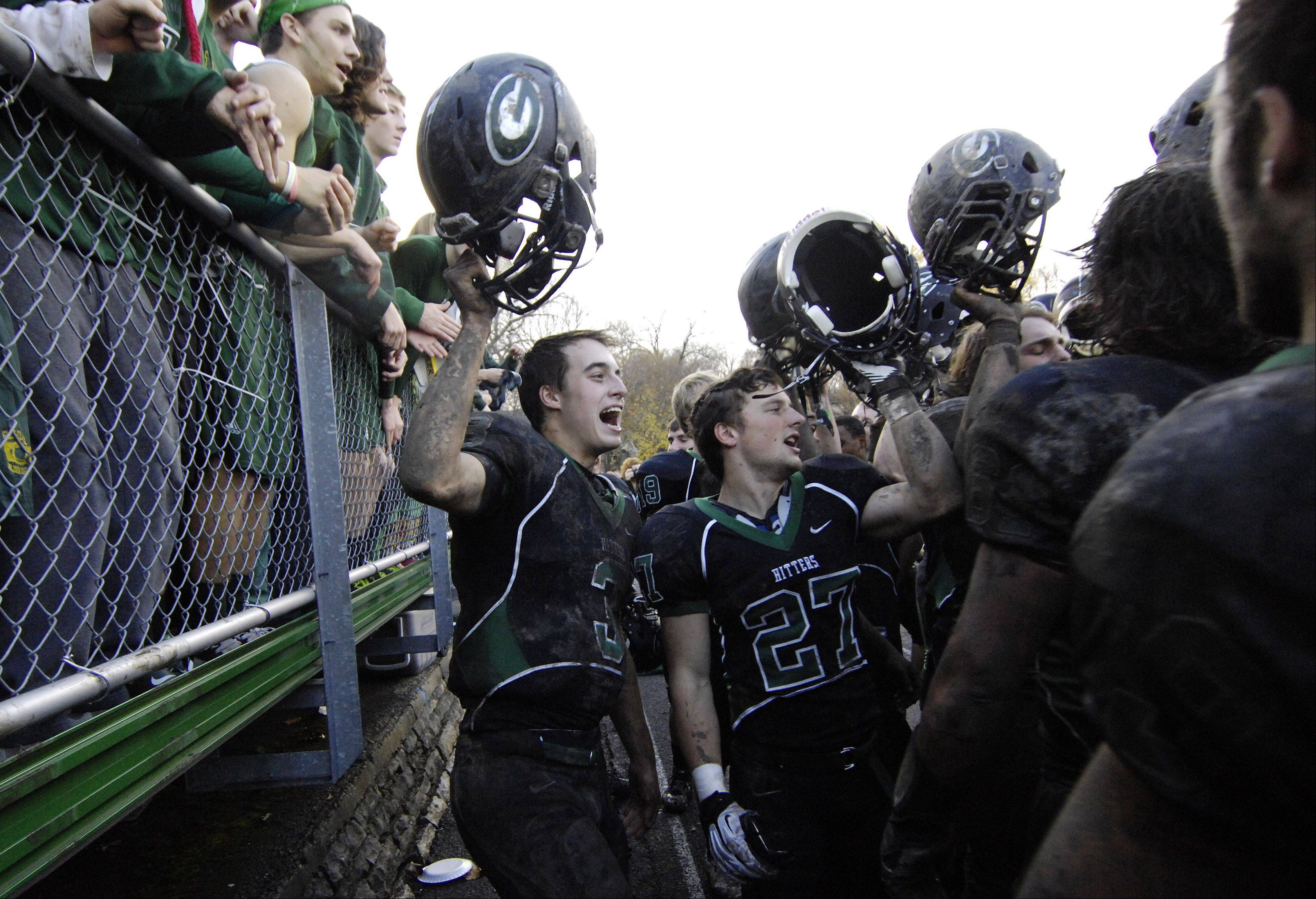 Glenbard West quarterback Henry Haeffner, left, celebrates with his teammates and fans from the student body following Saturday's 3-0 victory over Wheaton North.