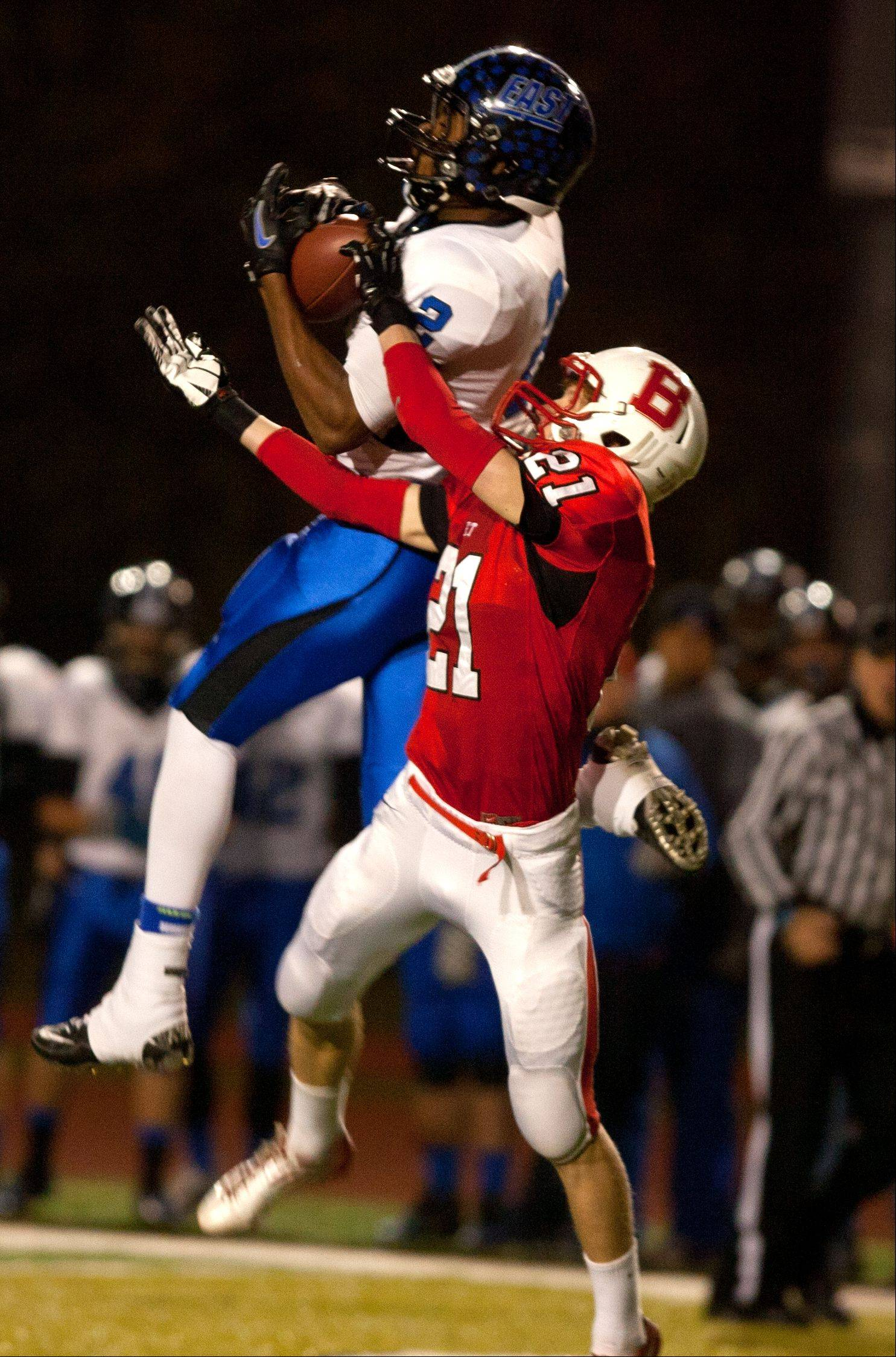 Benet's Ryan Parks (21) defends Lincoln-Way East's Justin Corbett (2), who caught a long third down pass during Class 7A football semifinals at Benedictine.