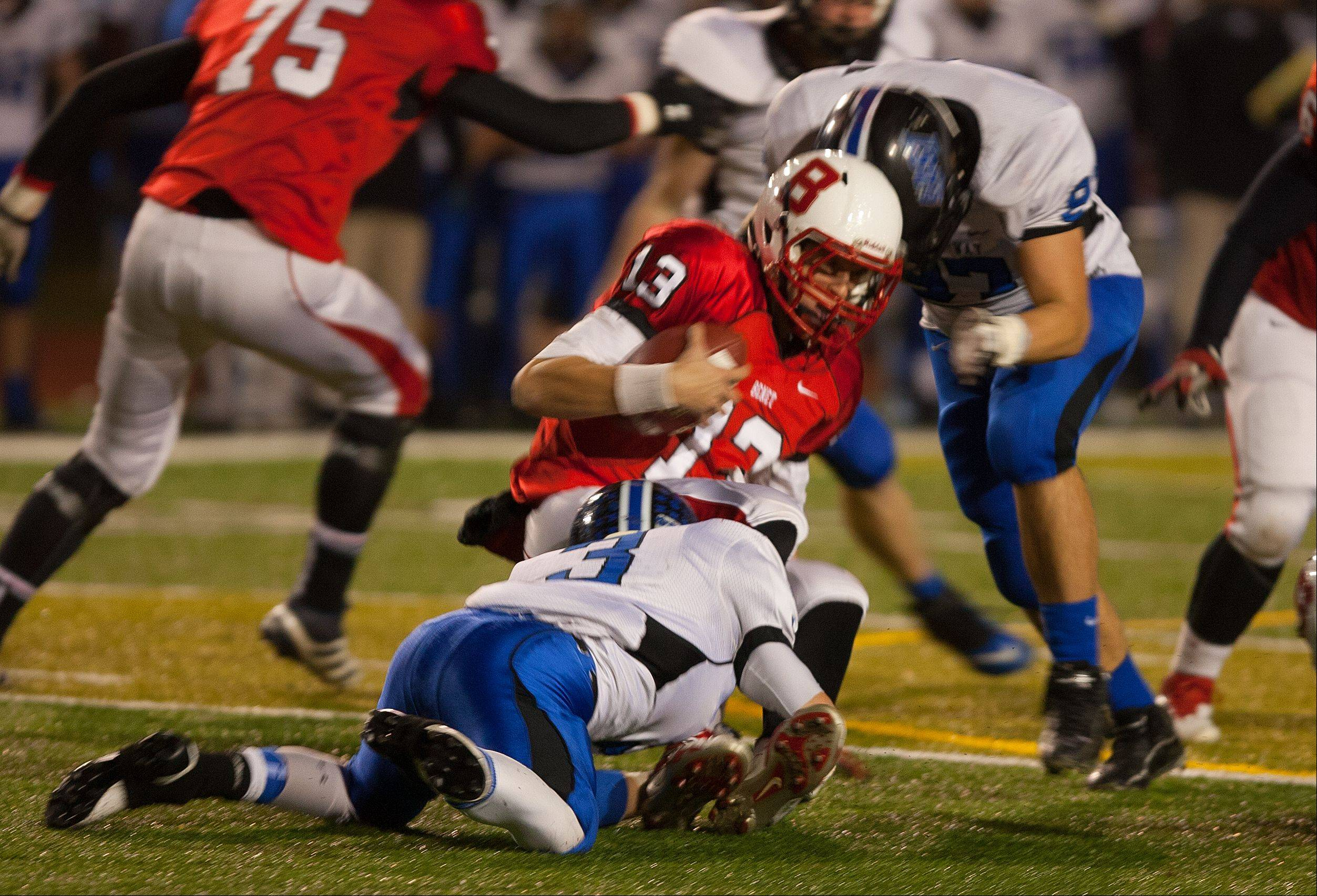 Benet quarterback Jack Beneventi (13) is tackled with an added personal foul by Lincoln-Way East's Scott Kresal (97), top, during Class 7A football semifinals at Benedictine.