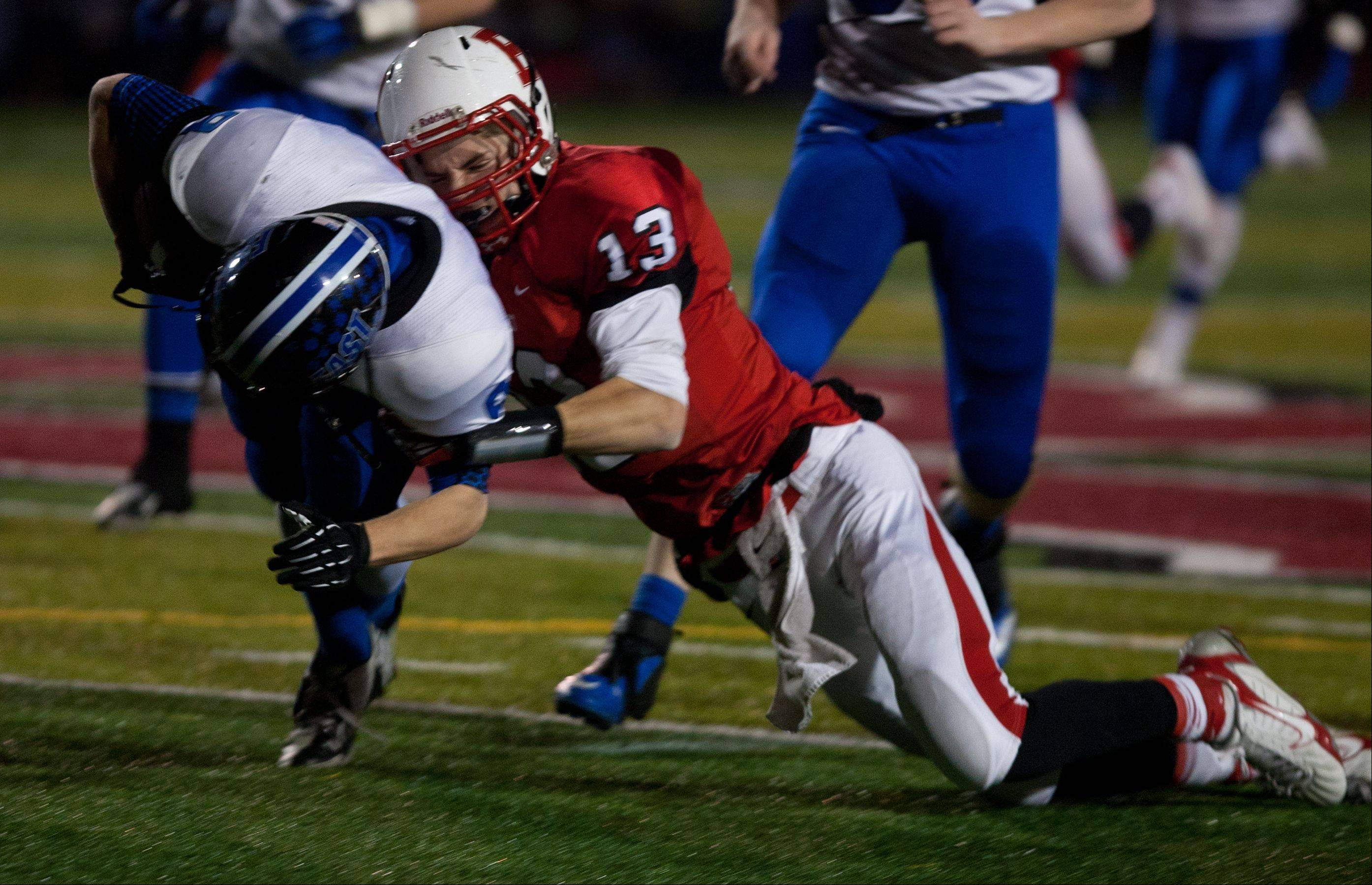 Benet quarterback Jack Beneventi (13) tackles Lincoln-Way East's Jordan Wirtz, who intercepted his pass during Class 7A football semifinals at Benedictine.