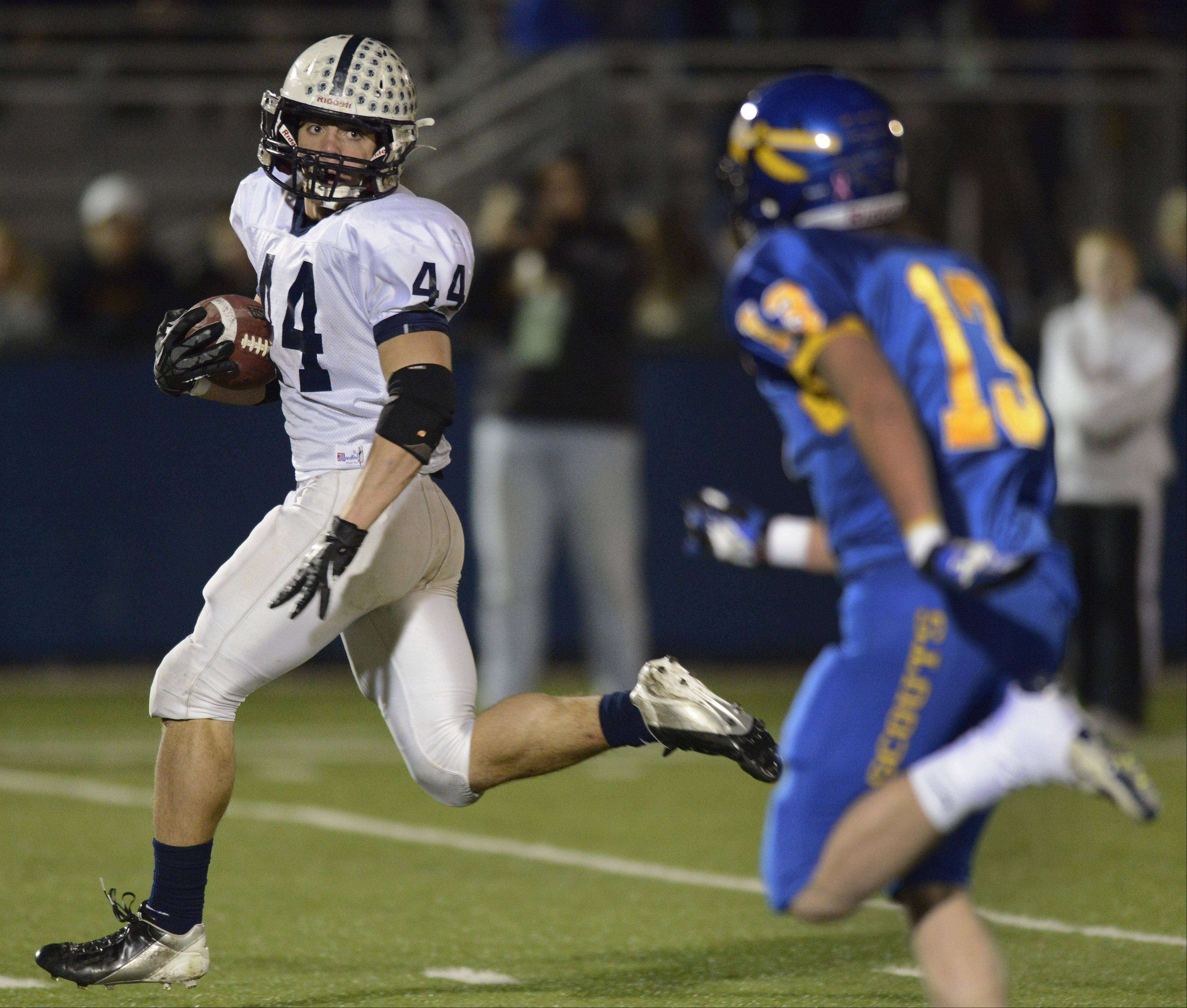Cary-Grove's Kyle Norberg (44) looks back at Lake Forest's Charles Moss, who is the closest defender, as he carries the ball for a touchdown during Saturday's Class 6A football semifinal in Lake Forest.