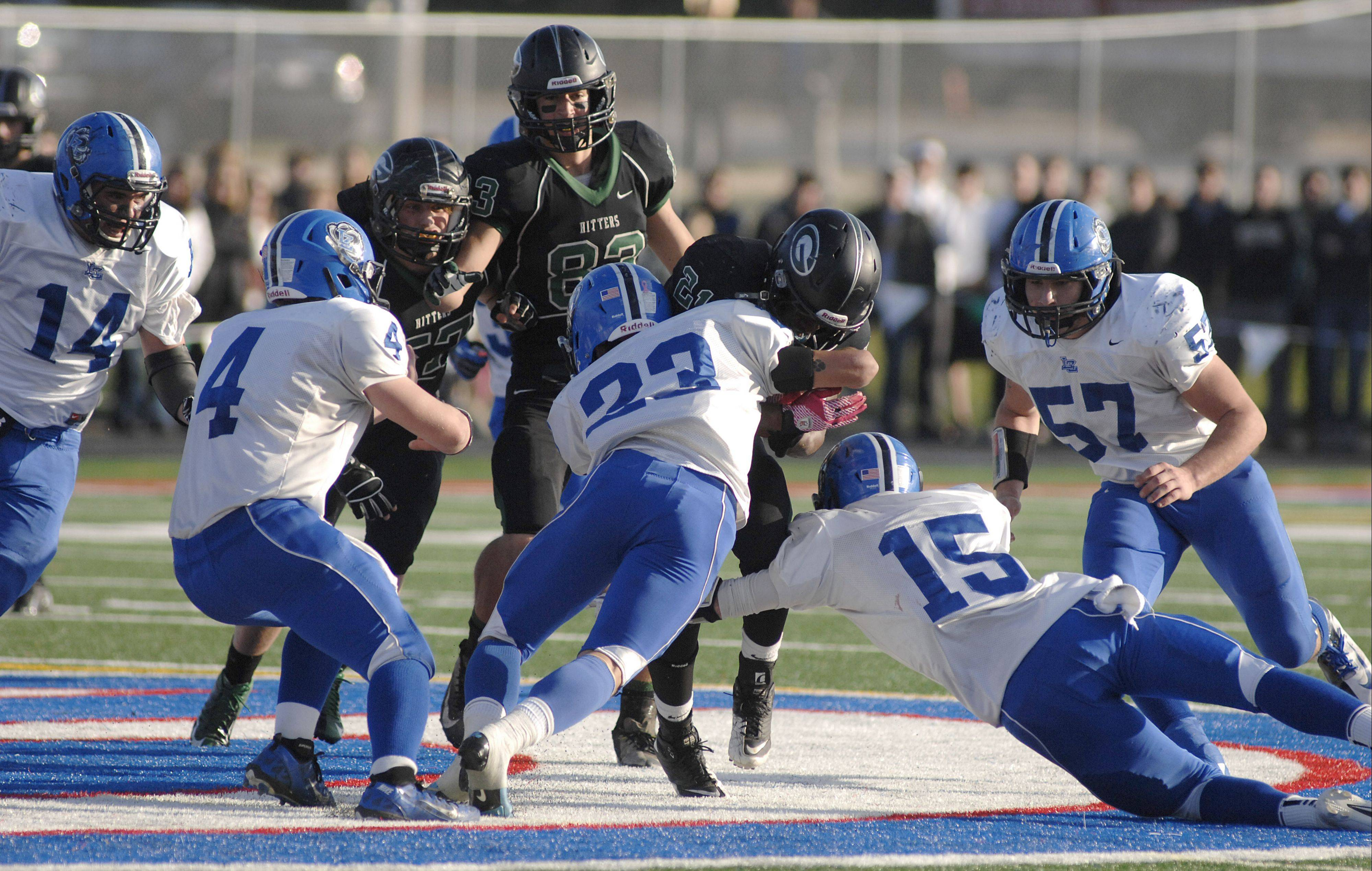 Glenbard West's Deon Dumas is stopped by Lake Zurich's Grant Soucy and Matt Moon in the third quarter on Saturday.