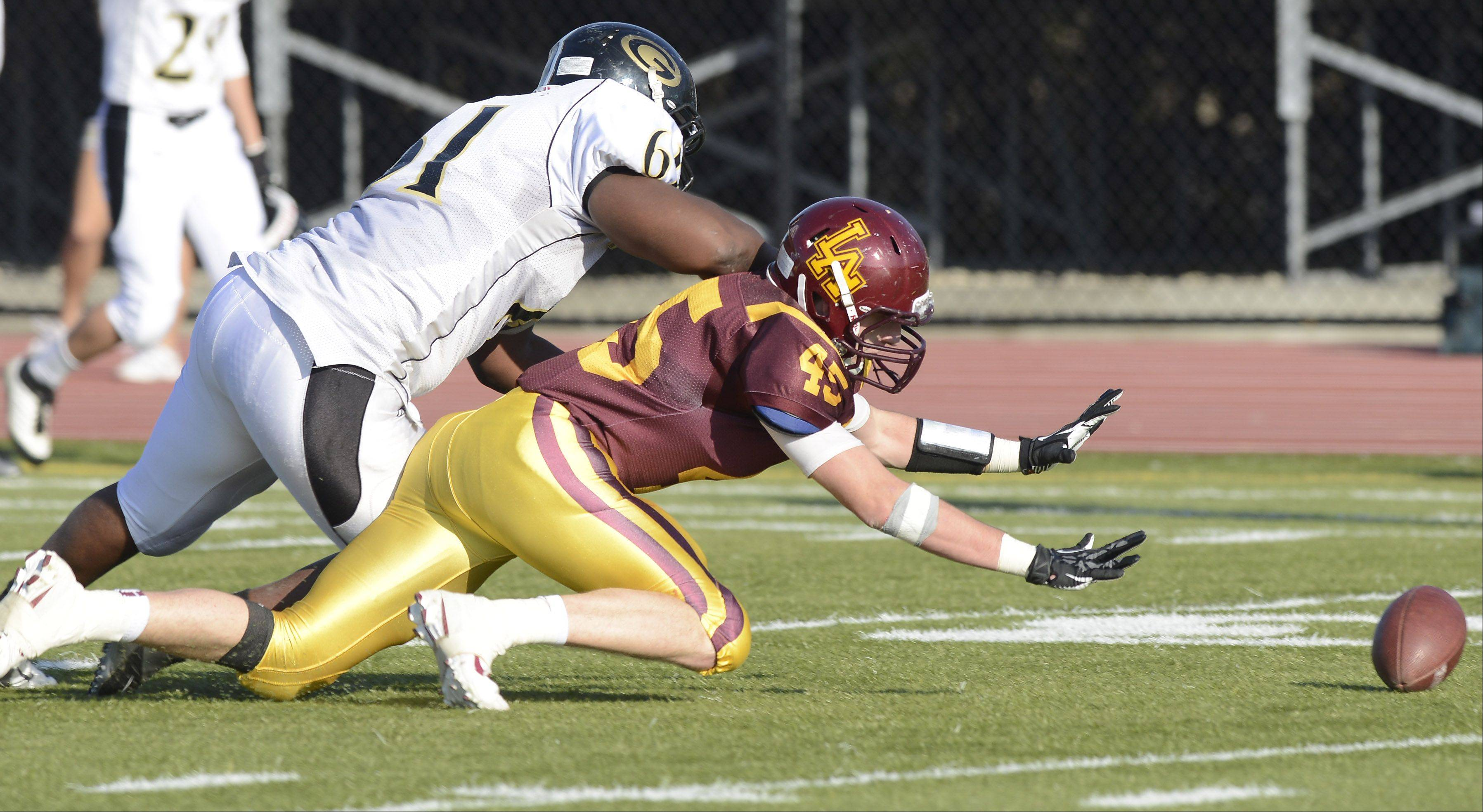 Glenbard North's D'Angelo Hodges, left, tries to fall on a fumble by his team as Loyola's James Trimble closes in on the ball during Saturday's class 8A football playoff semifinal. Glenbard North managed to recover on the play.