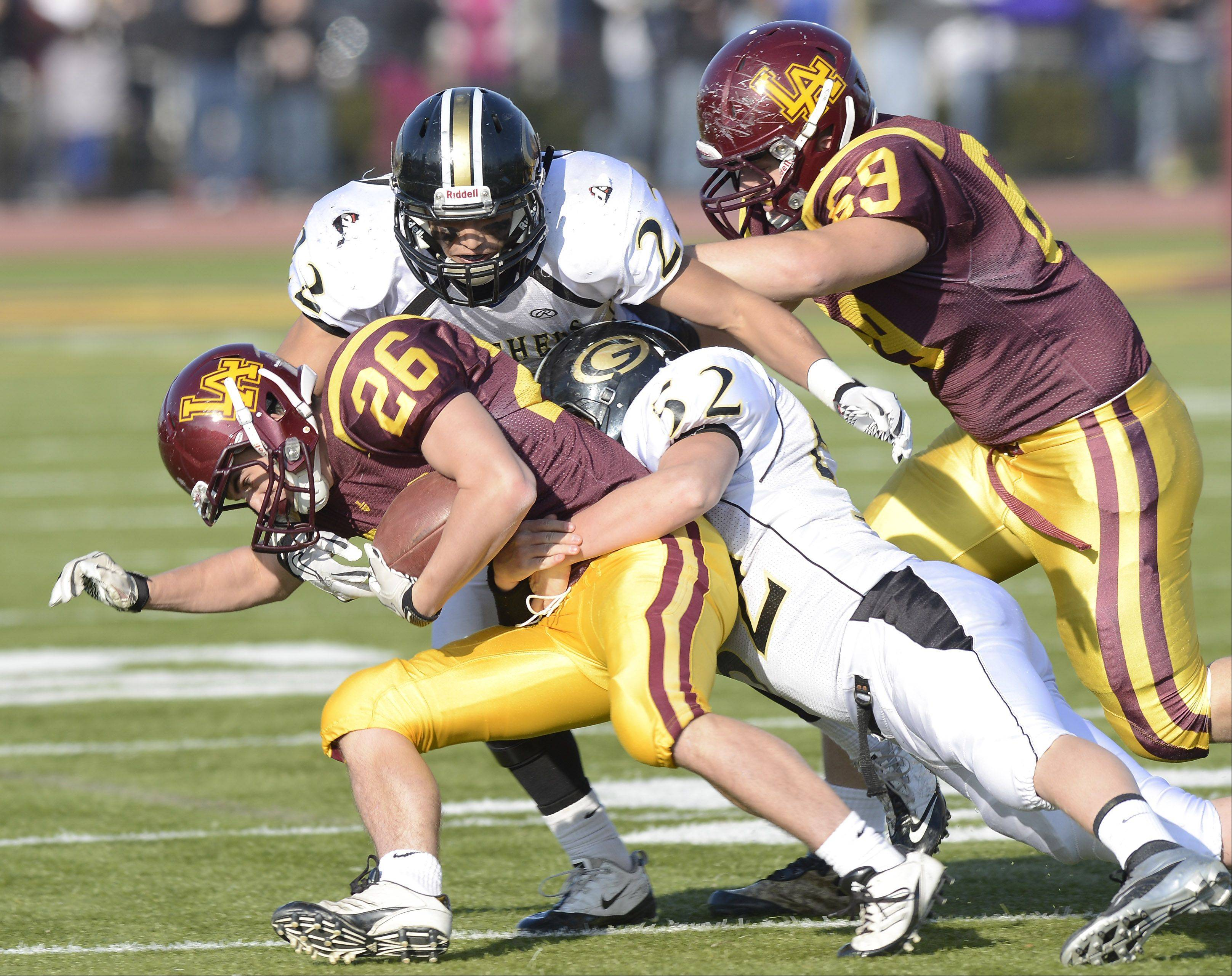 Loyola Academy's Johnny Burns gets tackled by Glenbard North's Mario Rodriguez, top, and Thomas Hood during Saturday's class 8A football playoff semifinal.