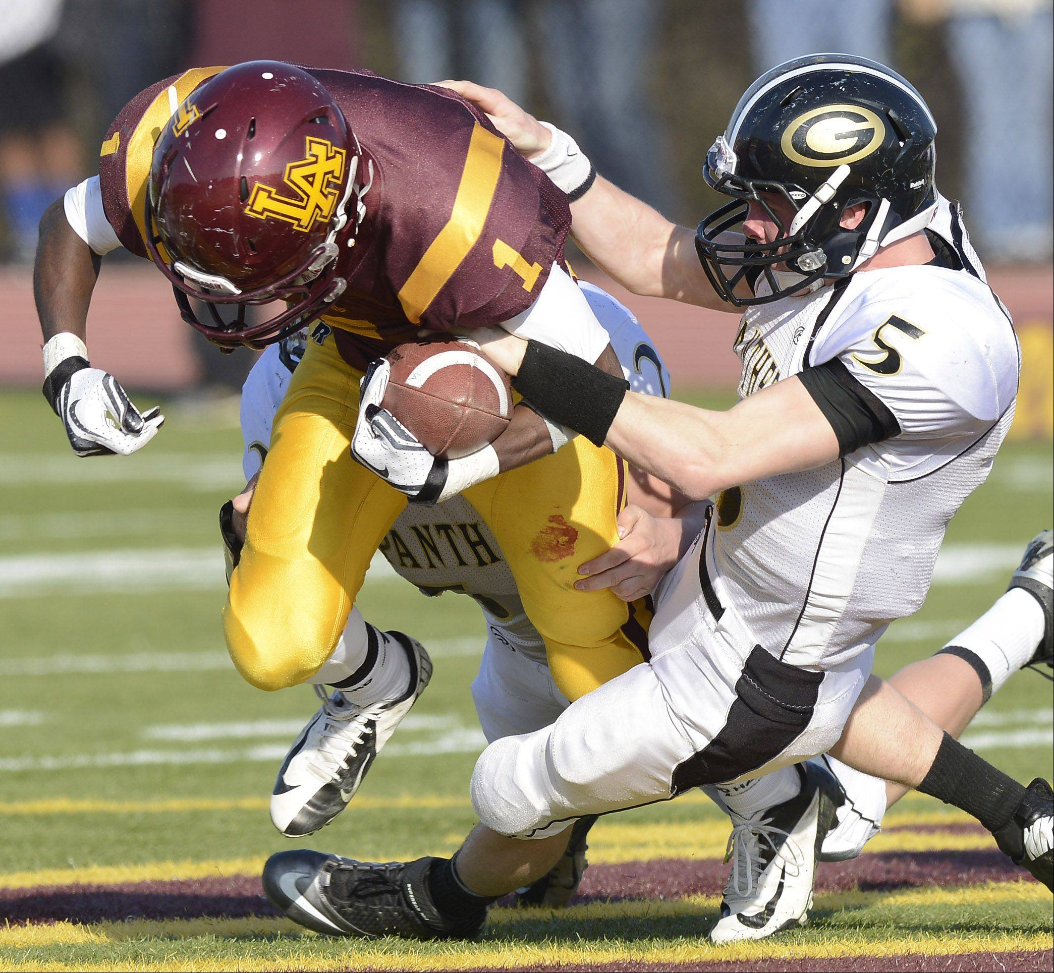 Glenbard North's Brian Murphy, right, tries to strip the ball from Loyola Academy's Kristopher Coker during Saturday's class 8A football playoff semifinal.