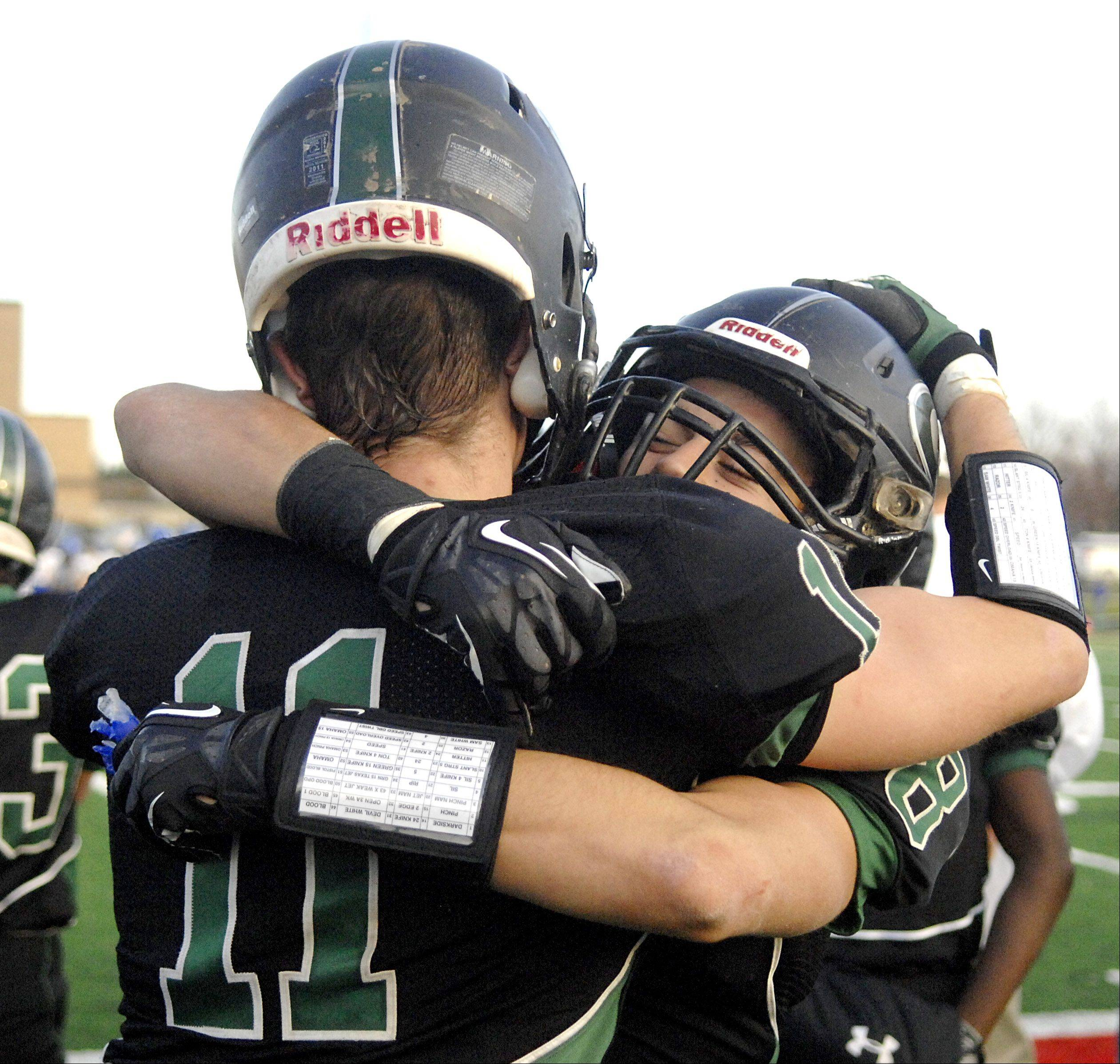 Glenbard West's Grant Greeno (11) gets a hug from teammate Hayden Carlson after their 7A semi final victory over Lake Zurich on Saturday, Nov. 17.