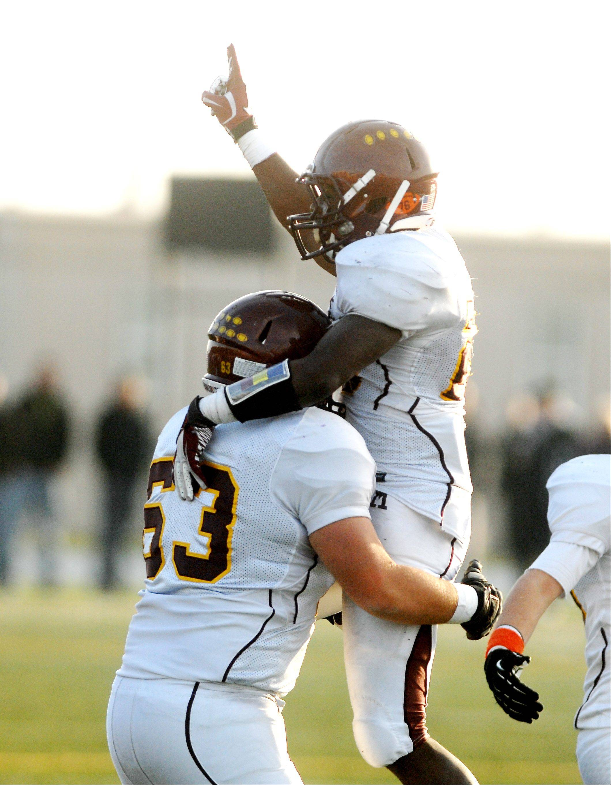 Michael Richmond holds Dimitri Taylor both of Montini after they sealed the win with a late touchdown during the Montini at Joliet Catholic Class 5A football semifinal Saturday.