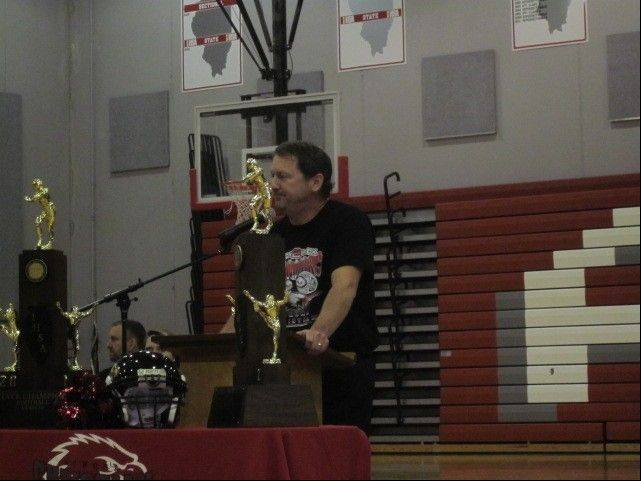 Aurora Christian School Eagles head coach Don Beebe addresses a welcome-home rally, flanked by the Eagles' two state-championship trophies, Saturday.