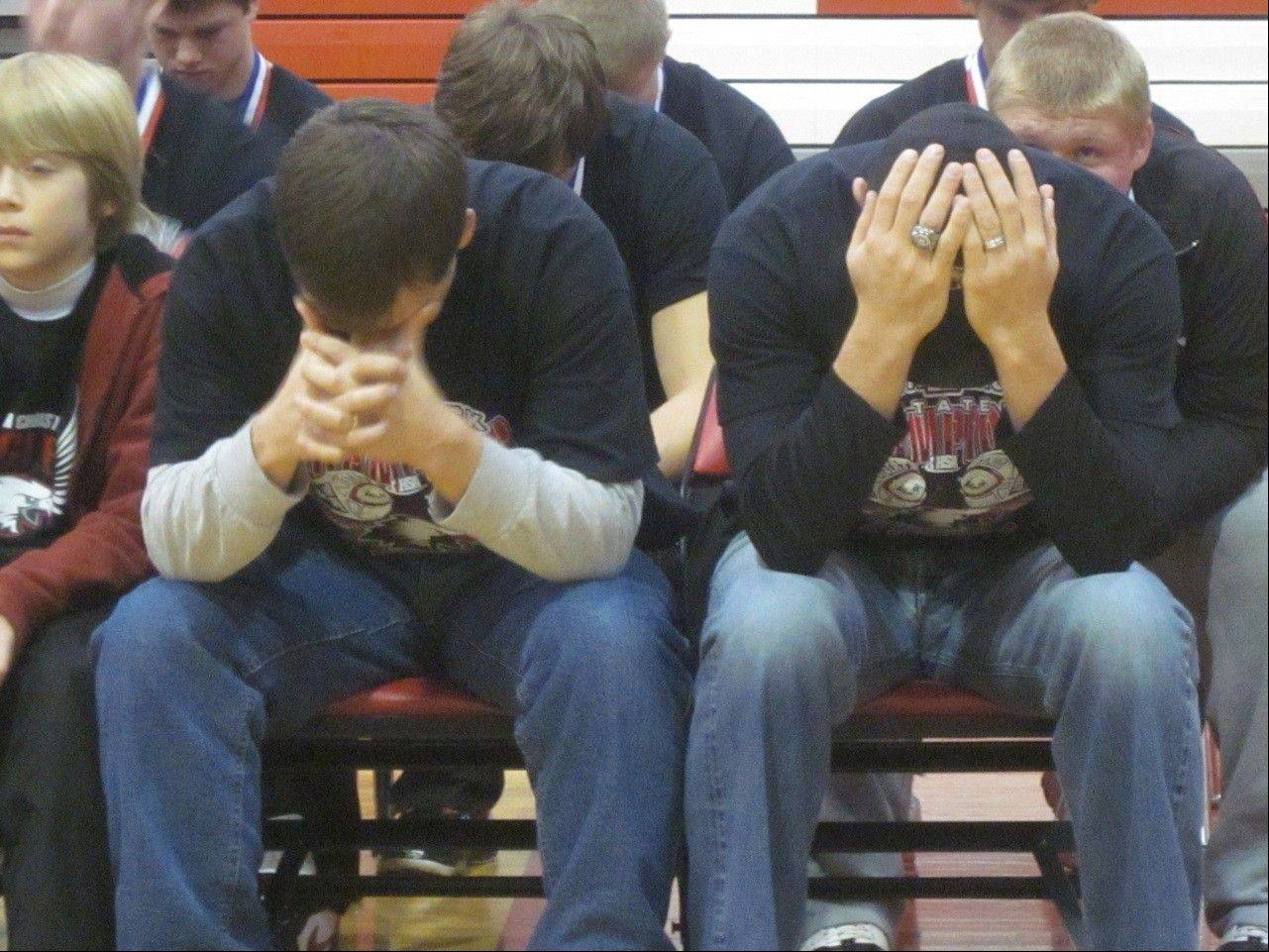 Aurora Christian Eagles defensive coordinator Dave Beebe, left, and assistant coach John Jira pray at a welcome-home rally for the Eagles Saturday. The team won its second consecutive state championship Friday.