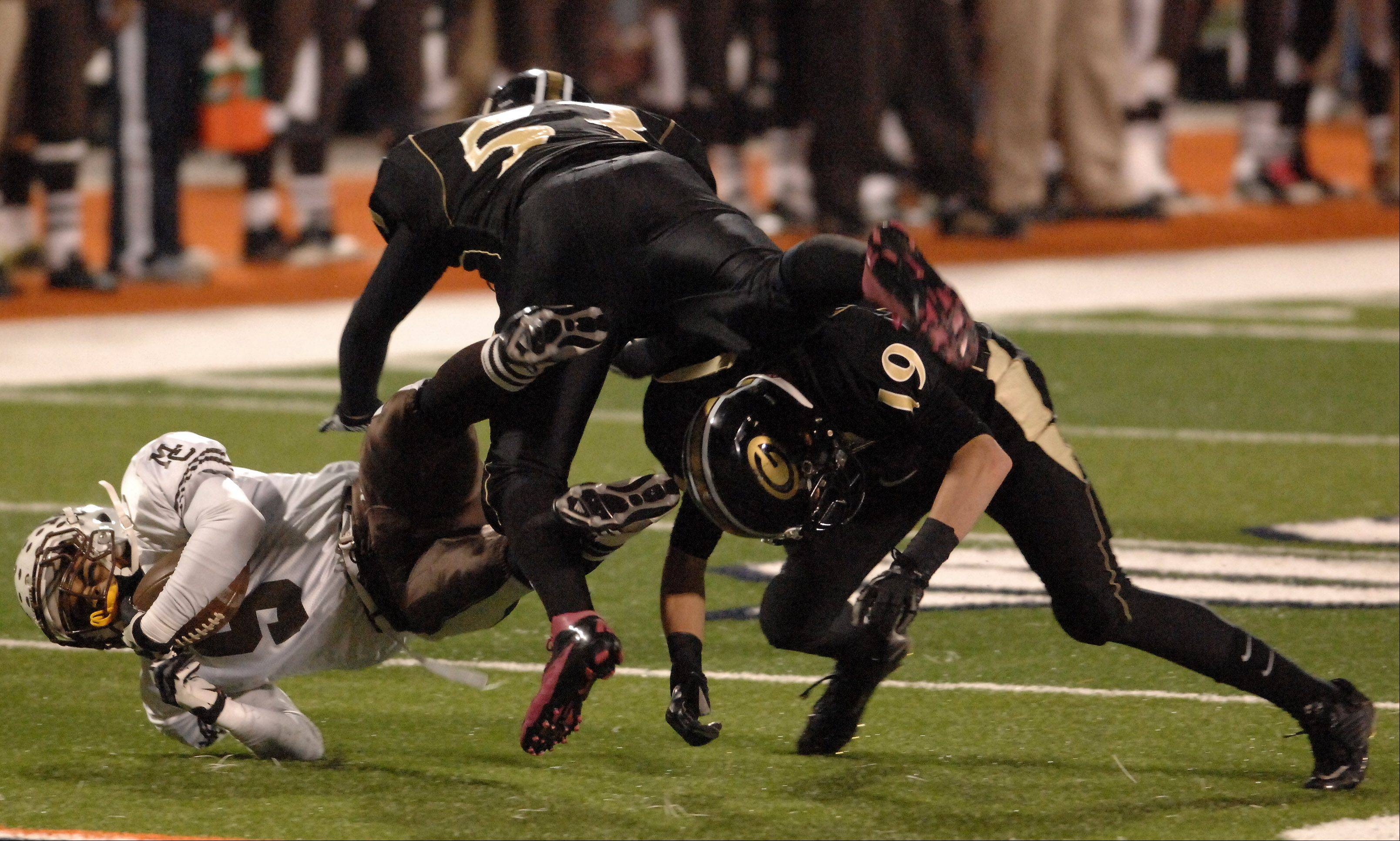 Glenbard North's Joe Fierro, 53, puts a big hit on Mt. Carmel's Ivan Strmic during Saturday's Class 8A state title game at Memorial Stadium in Champaign.
