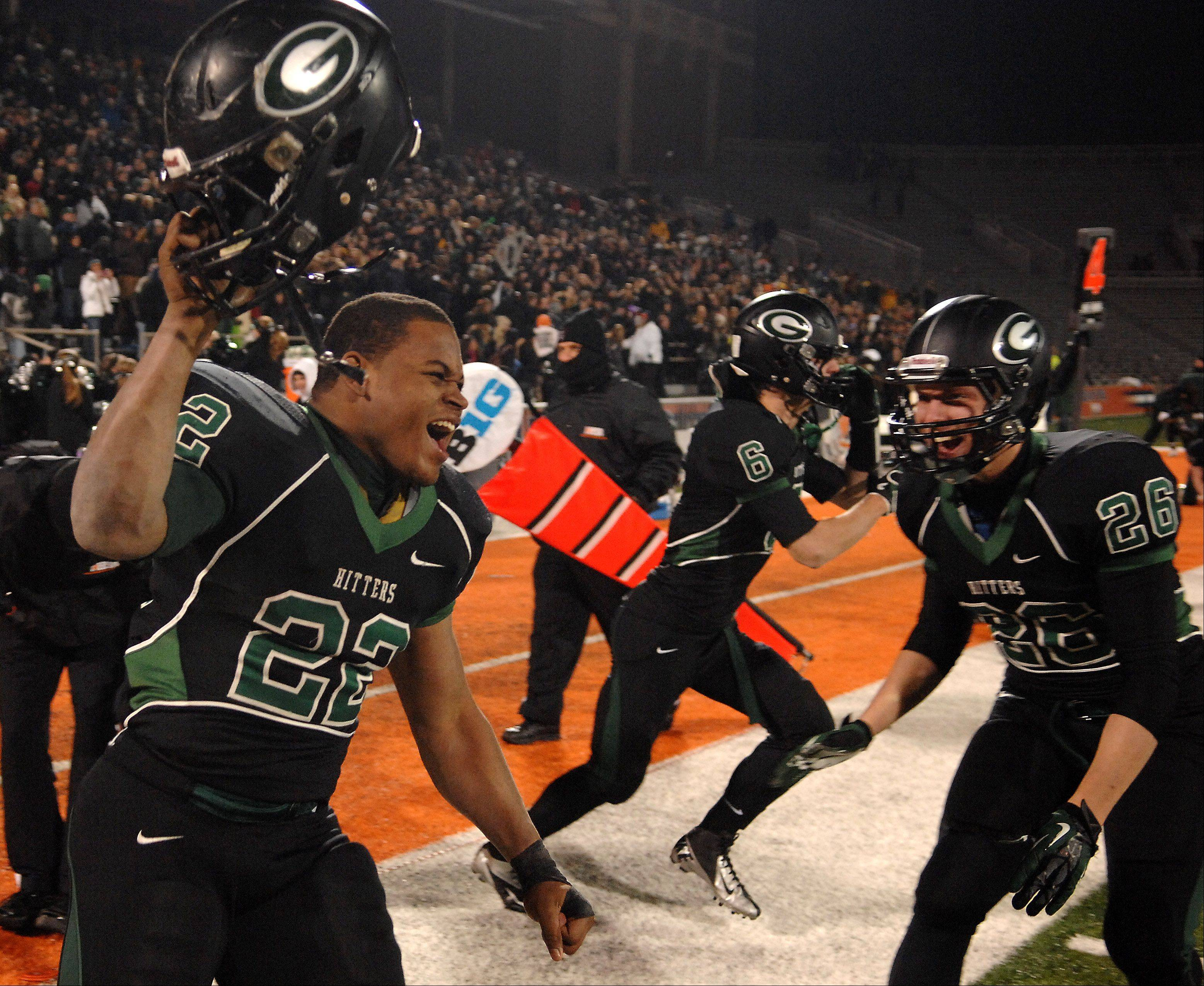 Glenbard West Devante Toney, 22, and his teammates erupt in excitement as the defense stops Lincoln-Way East as the clock expires during Saturday's Class 7A state title game at Memorial Stadium in Champaign.