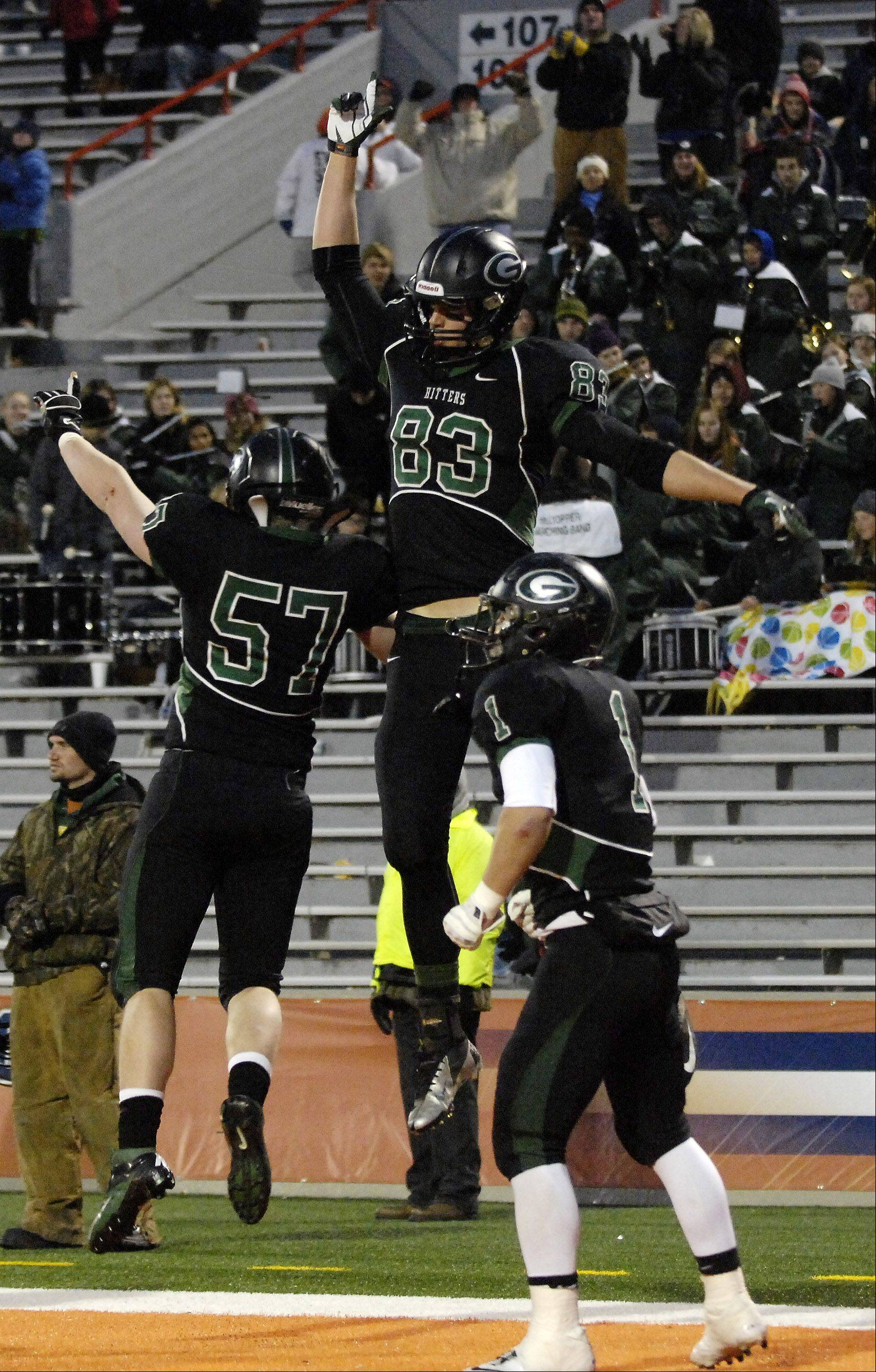 Glenbard West's Nathan Marcus, 83, celebrates his touchdown with teammates Jack Manzella, 57, and Joseph Zito during Saturday's Class 7A state title game at Memorial Stadium in Champaign.